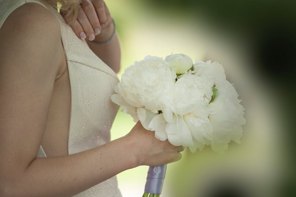 White - There's no reason why your dress needs to be the only white piece at your wedding. It's called a white wedding for a reason isn't it? White is classic, crisp and effortlessly elegant. Spring flowers such as roses, peonies and orchids look amazing when bunched together in a huge bouquet and can be so effective as solo pieces too. We've seen a rising trend in bridesmaids being all in white too, which if you don't mind sharing the spotlight makes for some seriously amazing photos.Opting for a white colour palette for your wedding makes for much easier decisions when dressing the room. Keep it simple with fabric draping everywhere.