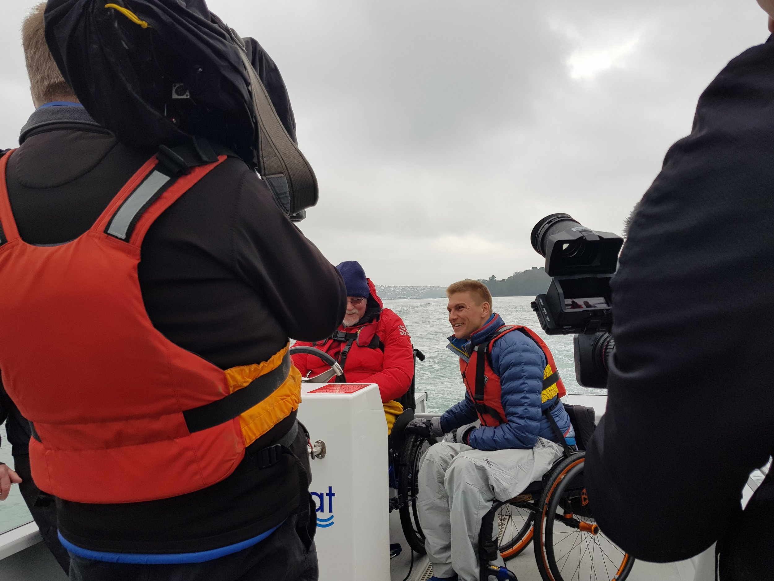Countryfile presenter, Steve Brown, interviews North Wales Sailability volunteer, Ian Roberts, at the V20's helm.
