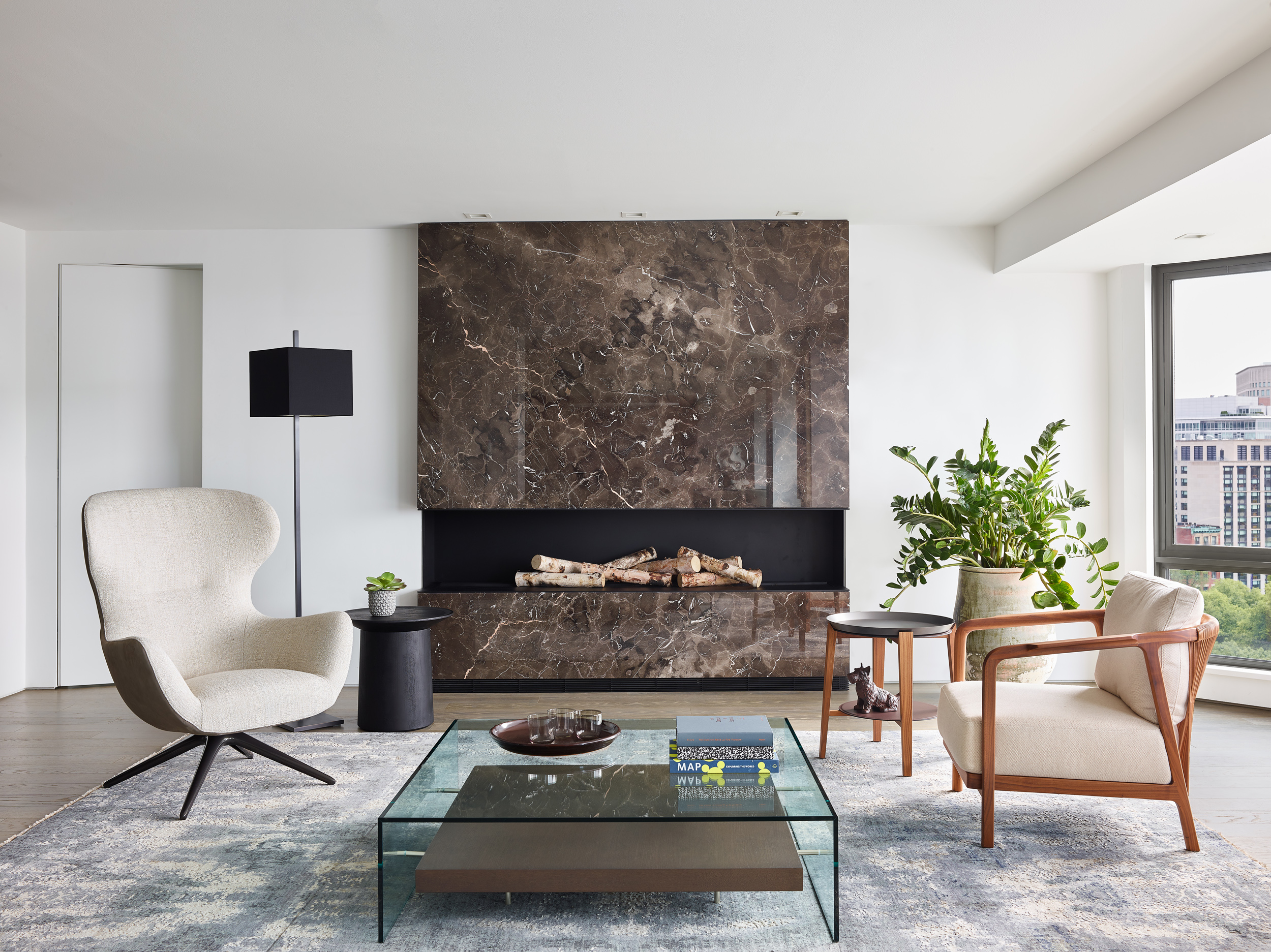 """DOWNTOWN LIVING   LOCATION Boston, MA  COMPLETED 2018  ARCHITECT & INTERIOR DESIGN Walker Architects  GENERAL CONTRACTOR The LaGasse Group  STONE SUPPLIER & FABRICATOR Cumar  PHOTOGRAPHER Jared Kuzia Photography    Our clients, downtown academics with grown children, sought to combine two mid-rise apartments to gain an unparalleled elevated view sweeping from the dome of the Boston State House westward to the riverfront campuses of MIT and Harvard. Because the owners were already comfortably at home in one of the apartments, the added second unit was designed as additional spaces for relaxation, with accommodations for billiards and darts, a seating area focused on a dramatic new fireplace, a sophisticated wine bar, and an adjacent study with sleek guest bath. New finishes were extended throughout the """"public"""" areas of the combined apartment, and include a newly paneled entry hall with concealed closets and a vegetated wall facing the front door.  In a home where the view is always going to be the star, new spaces are united in their modern simplicity, careful detailing and luxurious choices in materials. Anchoring a 45-foot long living room, a plane of warm brown marble is incised with a matte black steel fireplace that mimics the horizontal glow of the room's daily western sunsets. Nearby, wine is served on a white marble pattern-matched table, backed by a display of bottles in a conditioned """"cellar"""" lined with the same marble cut thin and backlit. Flanking the wine storage and display are paired dark bolivar cabinets housing serveries with concealed refrigeration and dishwashers. The guest bath, a study in smooth grey and white, features frameless glass, concealed ribbons of light and super-minimalist washbasins carved into a floating quartzite ledge. All spaces are wrapped in crisp white plaster without trim or baseboards, floating above a new floor of richly stained oak."""