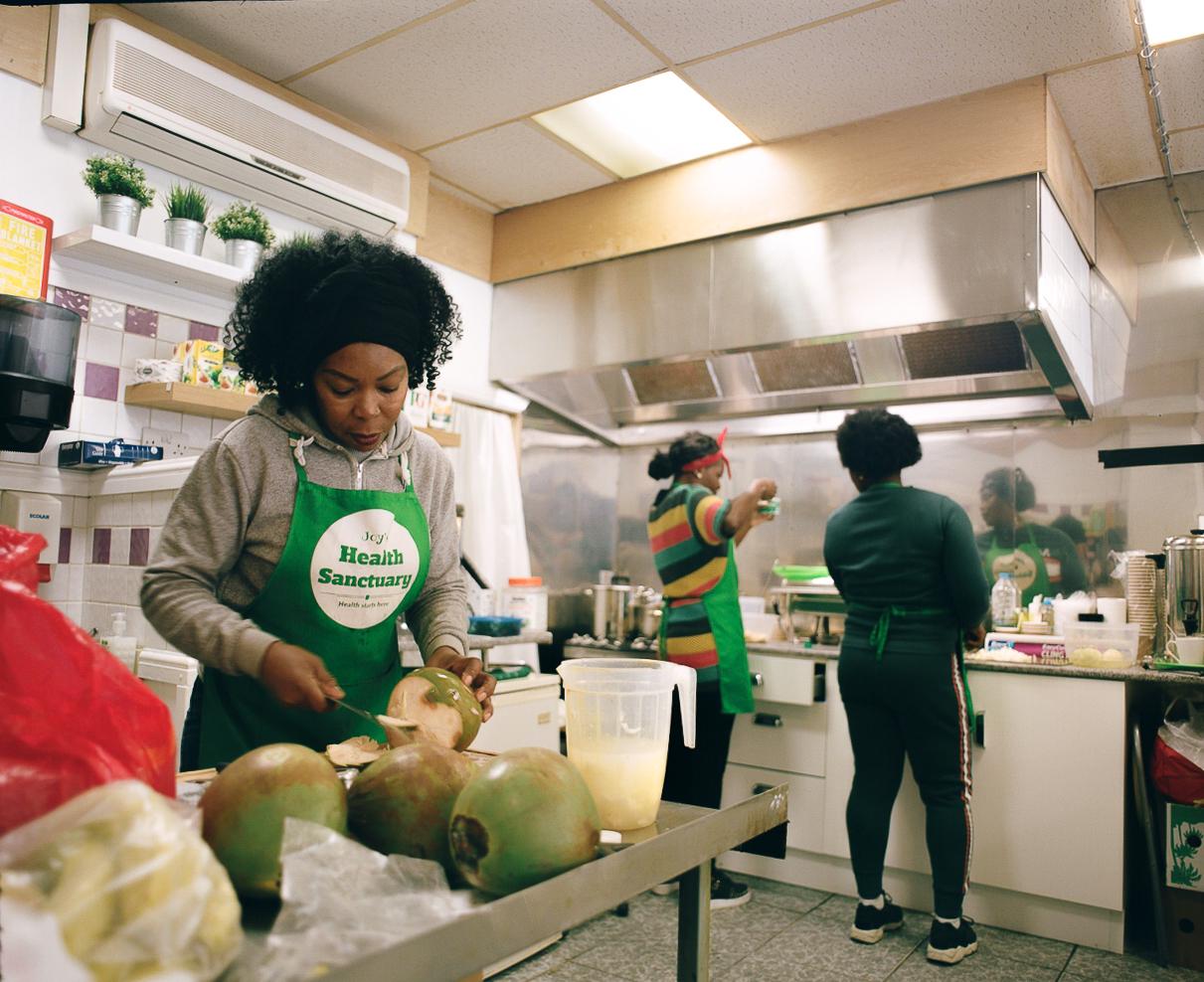 Joy (pictured far left) in her kitchen. Photo by Henry J Kamara.