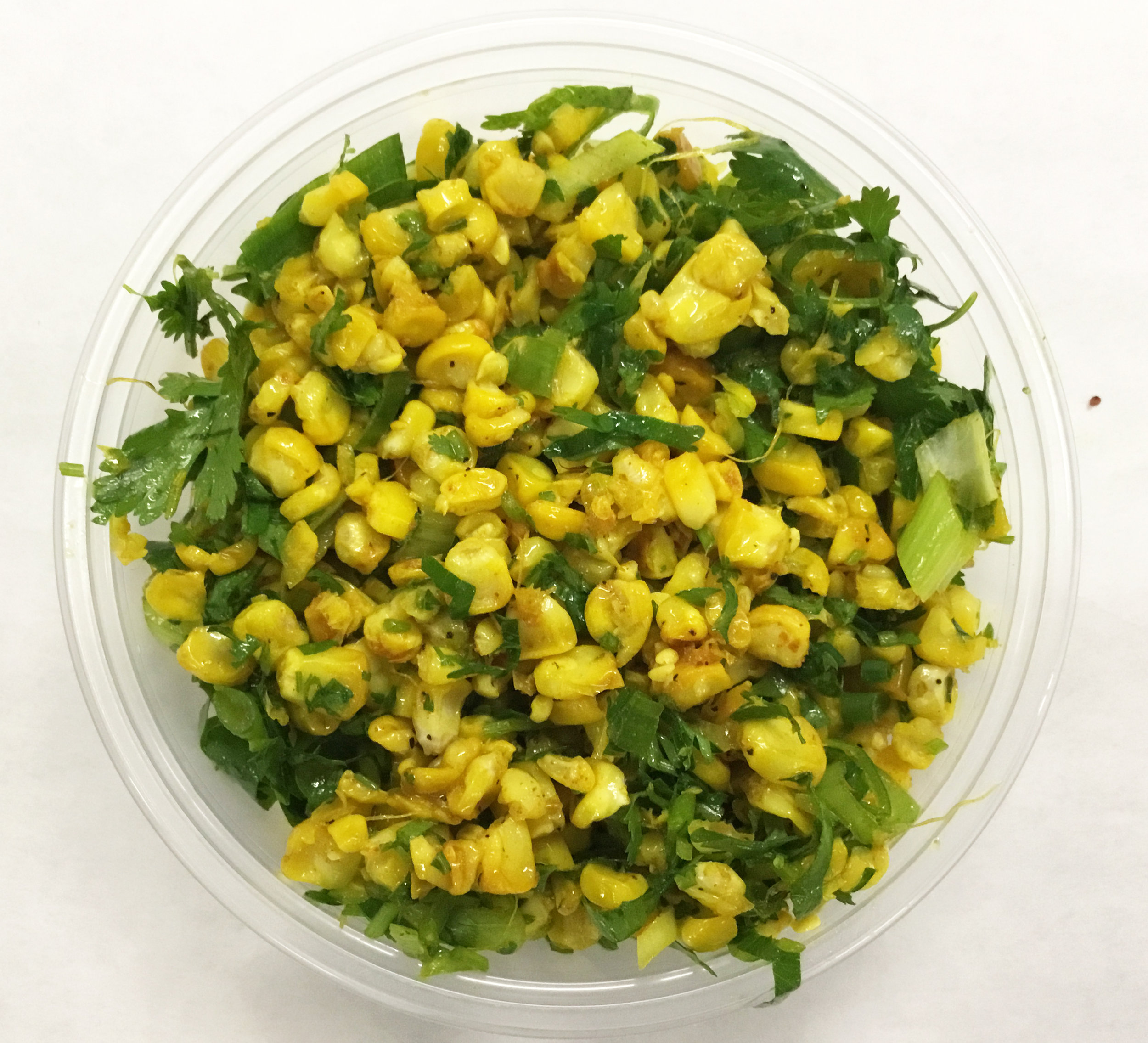 Fresh corn salad with parsley, cilantro, scallions and curry.