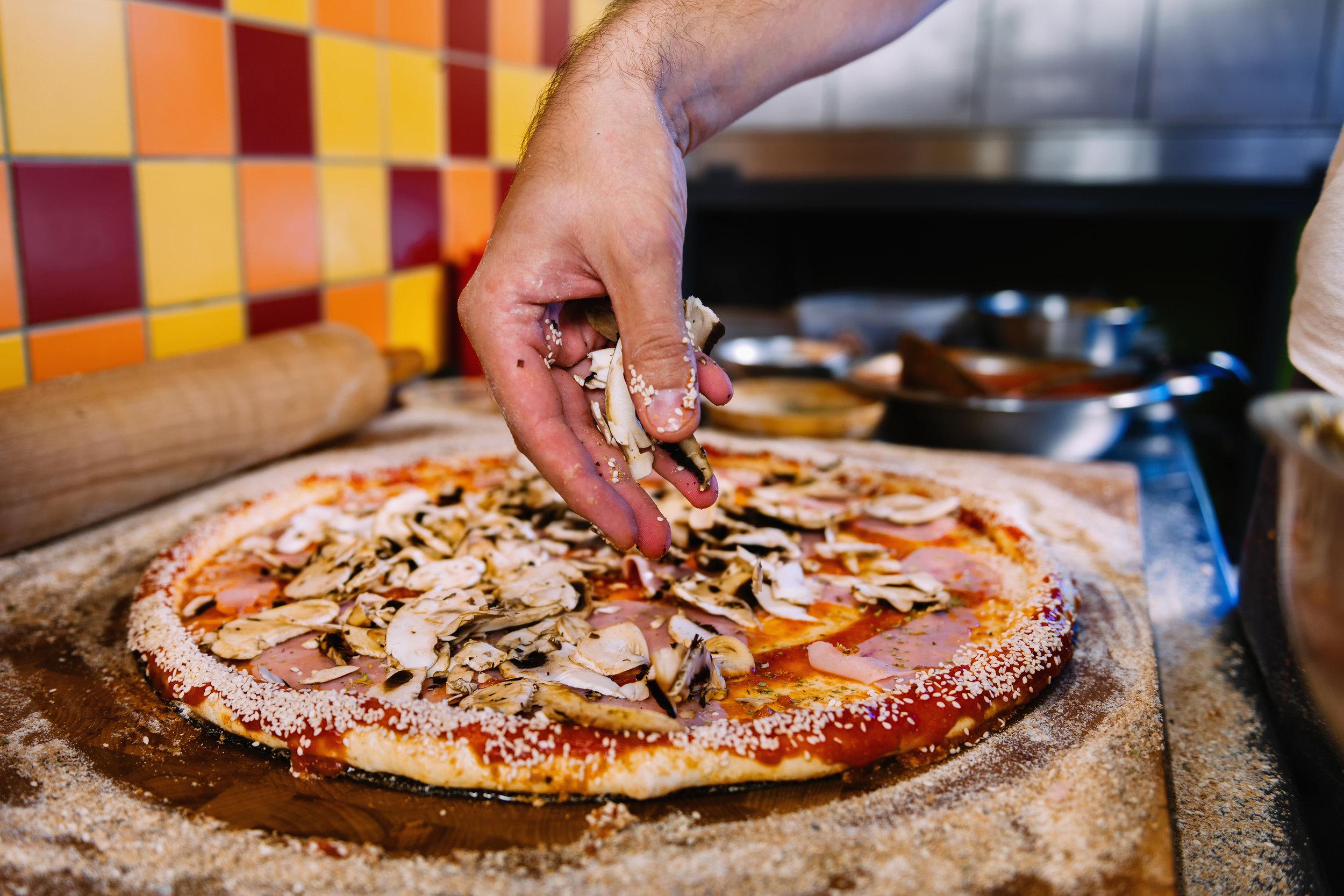 bigstock-Putting-Mushrooms-On-Pizza-In--259090804.jpg