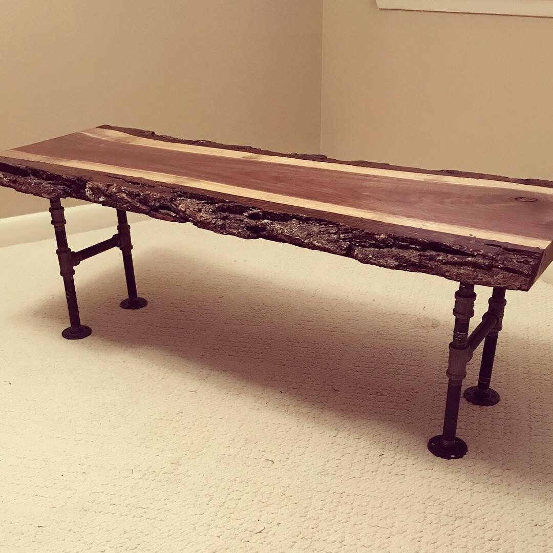 Black Walnut bench - This Barked live edge slab has black iron pipe legs to make for a heavy and sturdy piece.