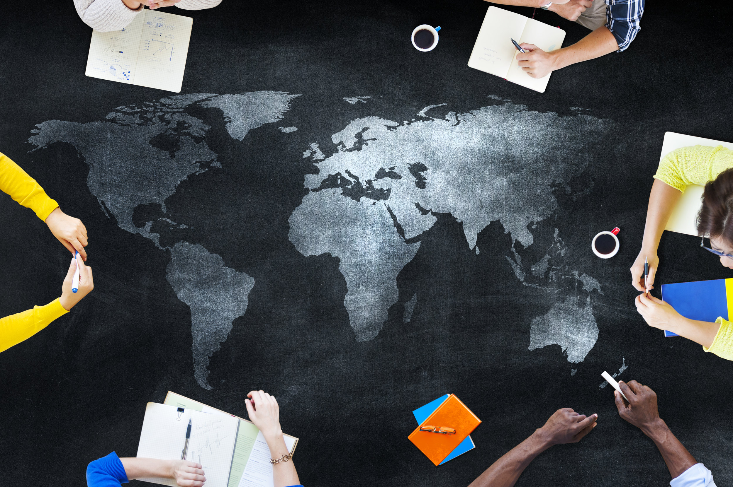people with notebooks seated at a black and silver world map