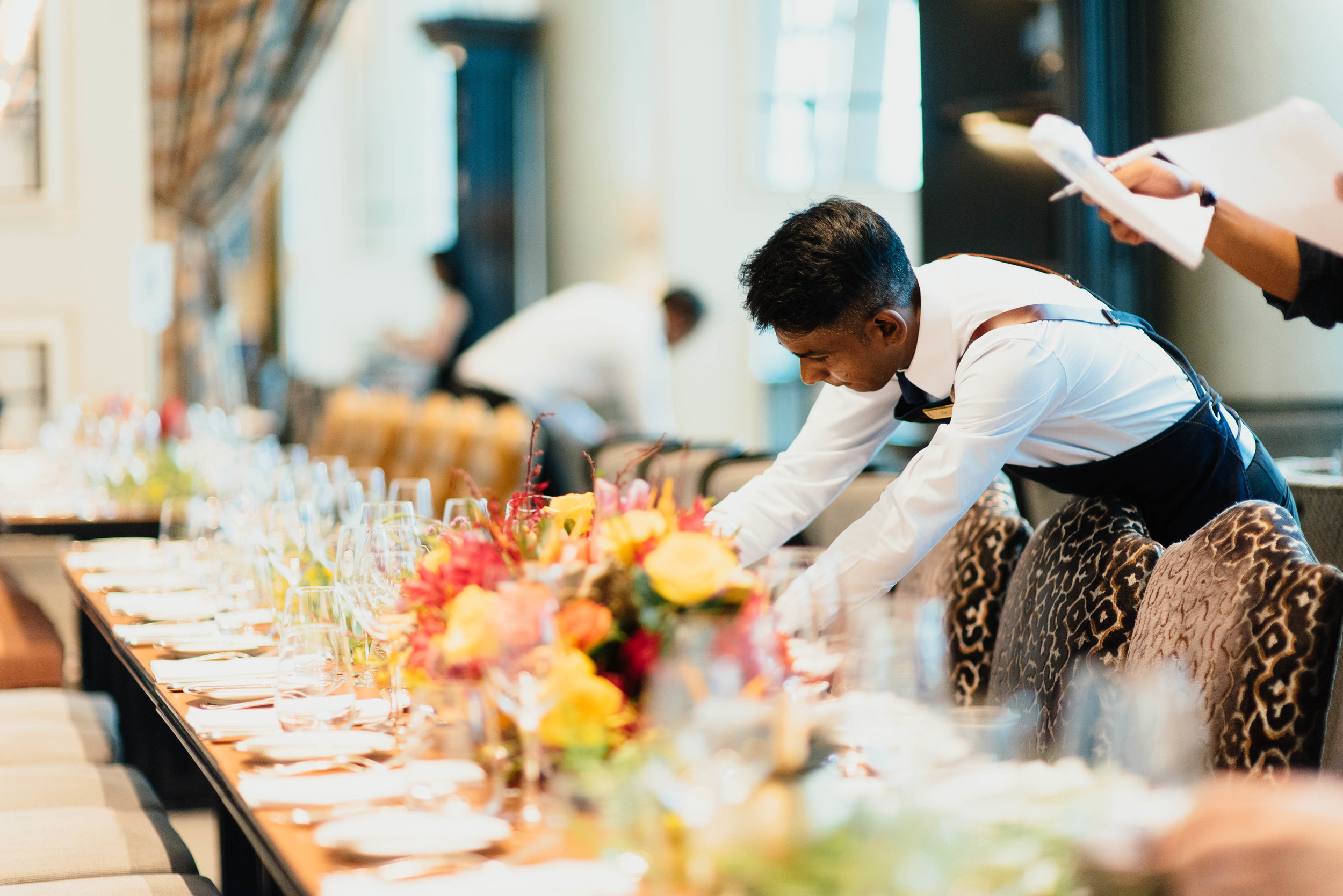 waiter fixing place setting at a banquet table