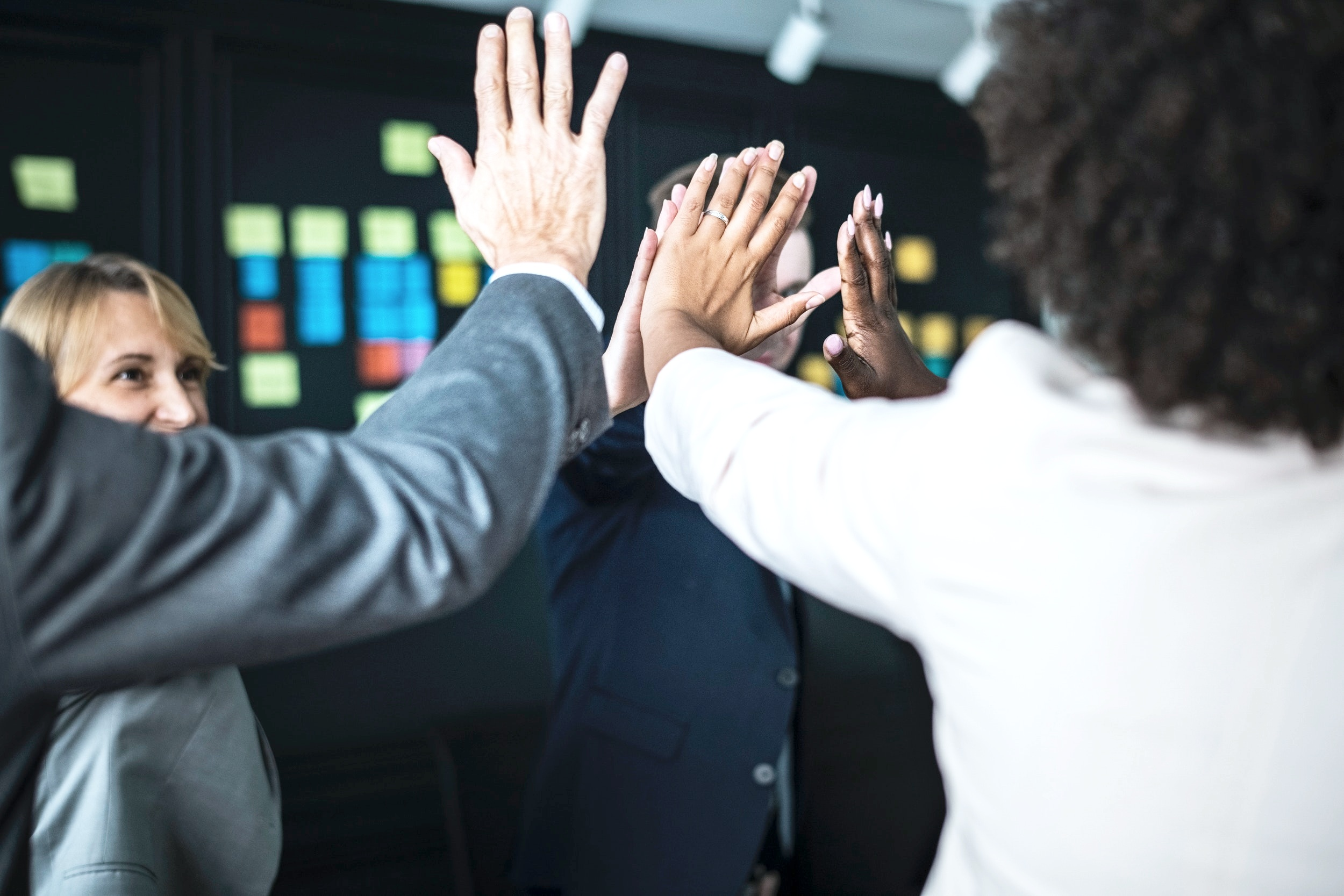 five people in office attire giving a high five in a circle
