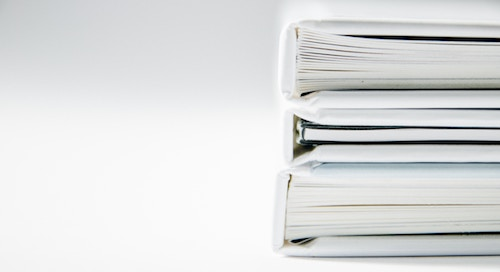 Stack of white binders filled with papers and documents