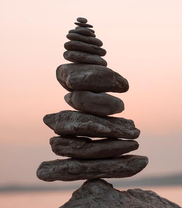 Stones balancing on a rock at sunset.