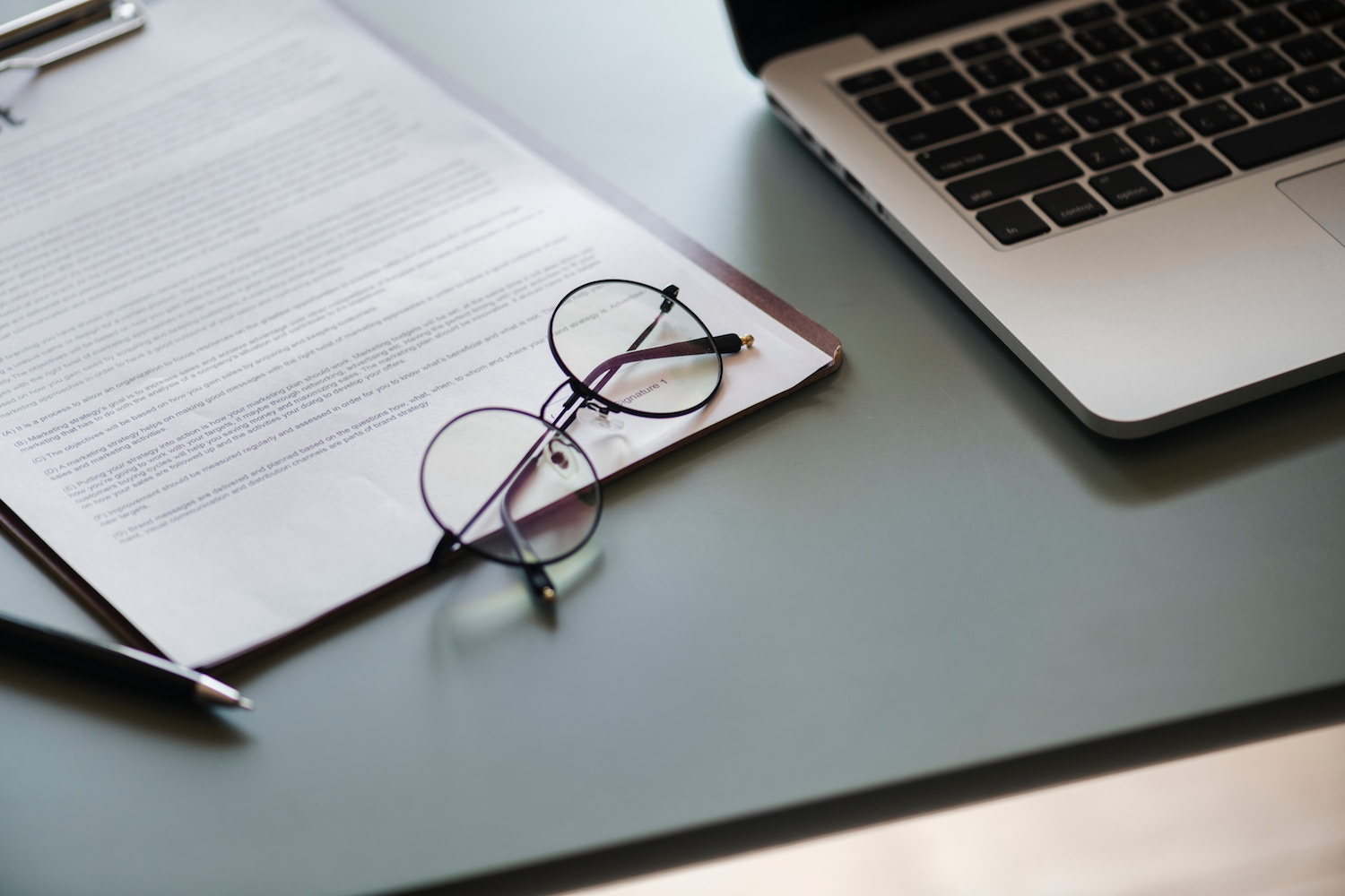 Round eyeglasses on top of business documents with a pen and laptop nearby.