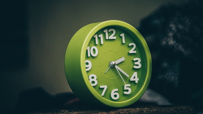 Green clock with white numbers and hands.
