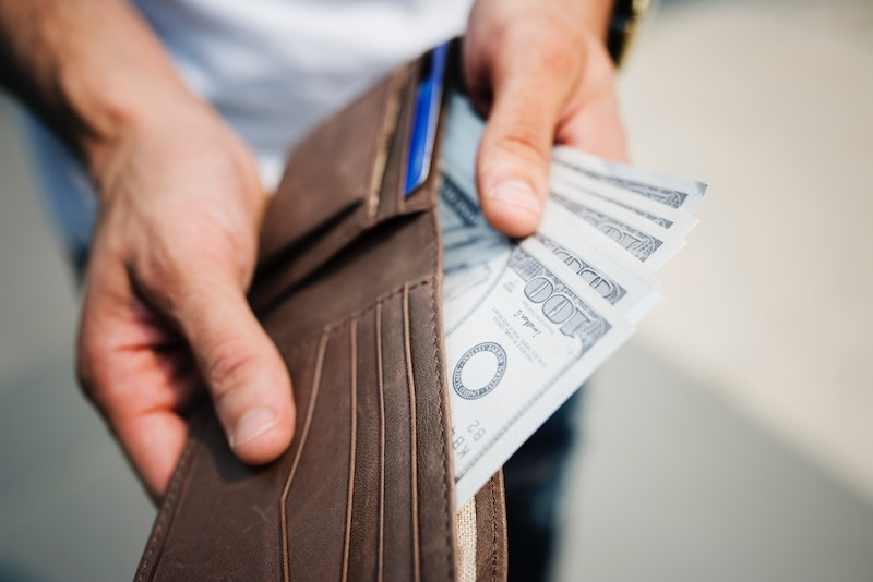 Person holding a brown leather wallet containing dollar bills.
