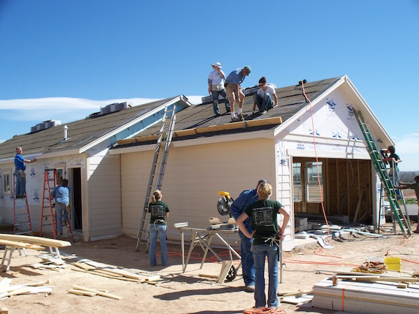 People climbing ladders and nailing shingles to the roof of a Habitat for Humanity house.