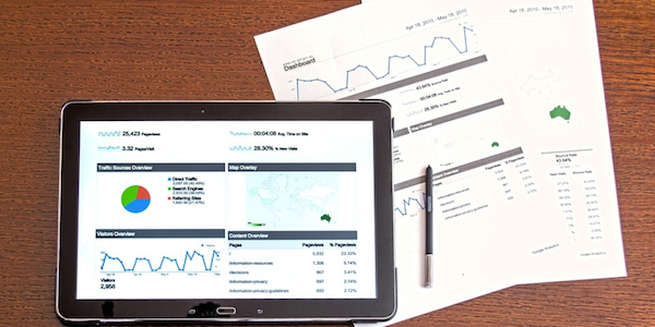 Financial reports presented on a digital tablet and paper.