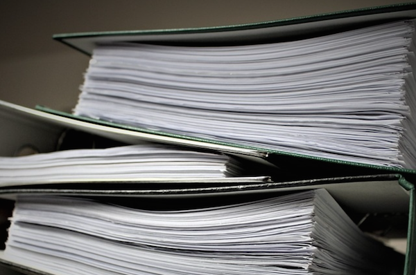 Stack of binders filled with paper forms.
