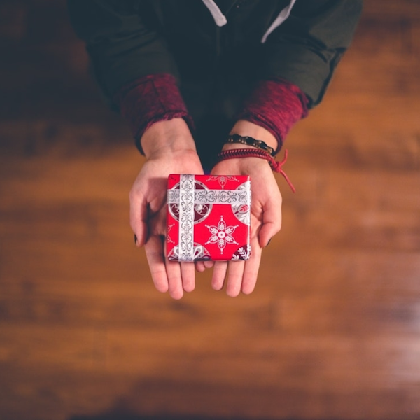 Person holding a gift wrapped in red paper and ribbon.