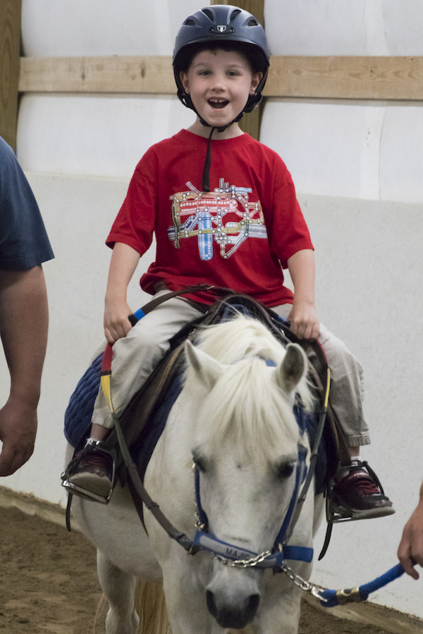 Child riding a TRI therapy horse.