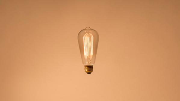 Lightbulb hanging against a blush pink background.