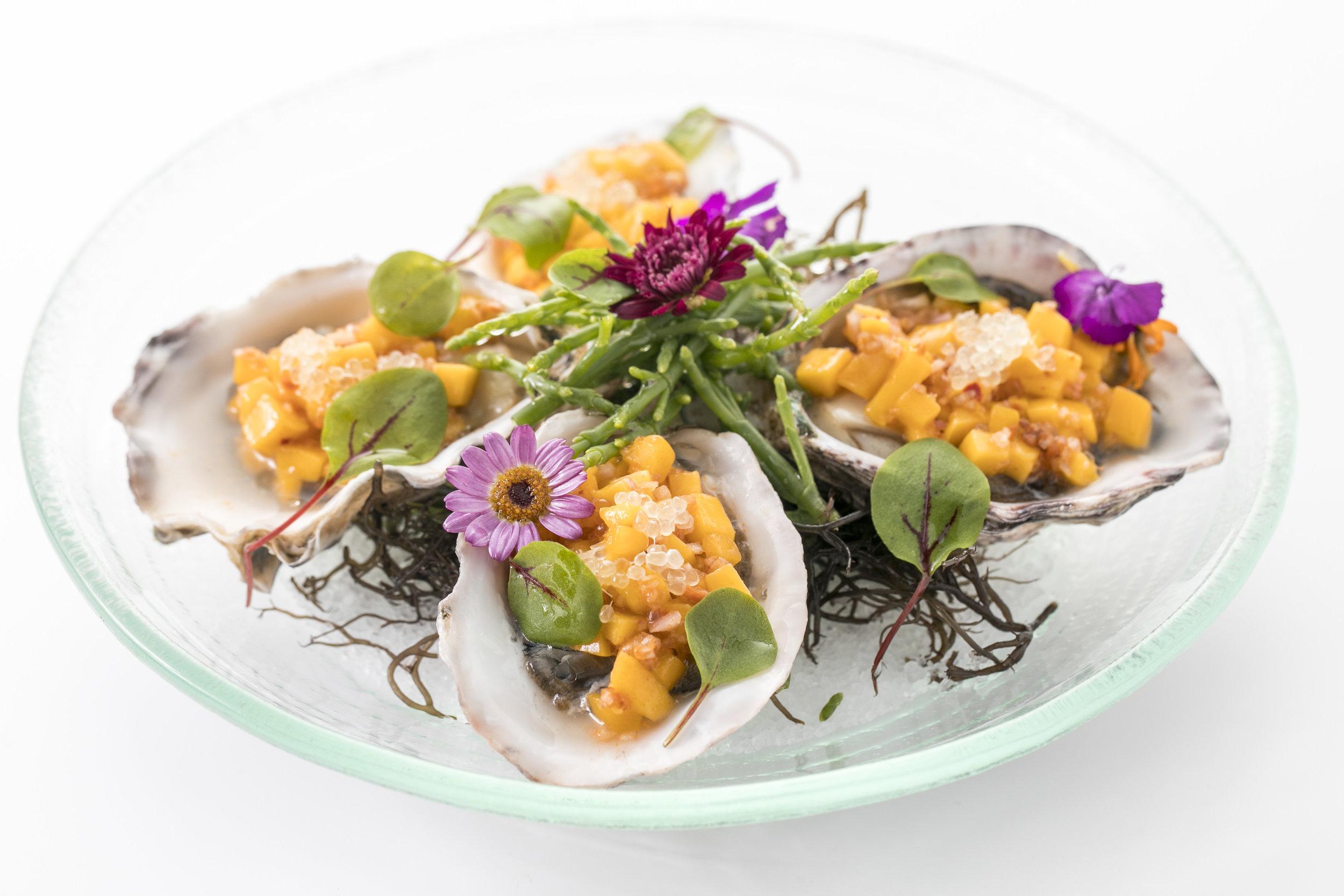 Oyster Mignonette オイスター・ミニョネッテ($24)   新鮮なファニーベイ・オイスター4個にイタリア、カラブリア産のポークサラミスプレッドとシーアスパラガスやオゴを乗せ、仕上げに食用フラワーをトッピング。食材の持つ自然の甘みと滋味、塩味が絶妙な逸品。1個$6で追加オーダーも可能。