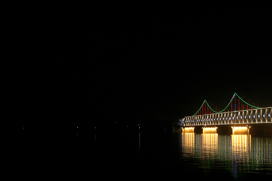 The Sino-Korean Friendship Bridge spans the Yalu River from Dandong, China, to Sinuiju, North Korea. At the time of this photograph in 2006, it was lit only on the Chinese side. © Laura Elizabeth Pohl