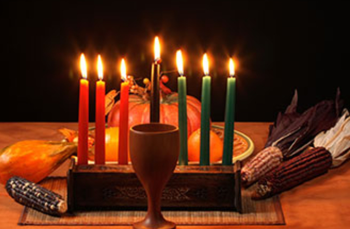 The seven symbols of Kwanzaa: unity cup, candle holder, straw mat, 7 candles, ears of corn, crops, gifts.