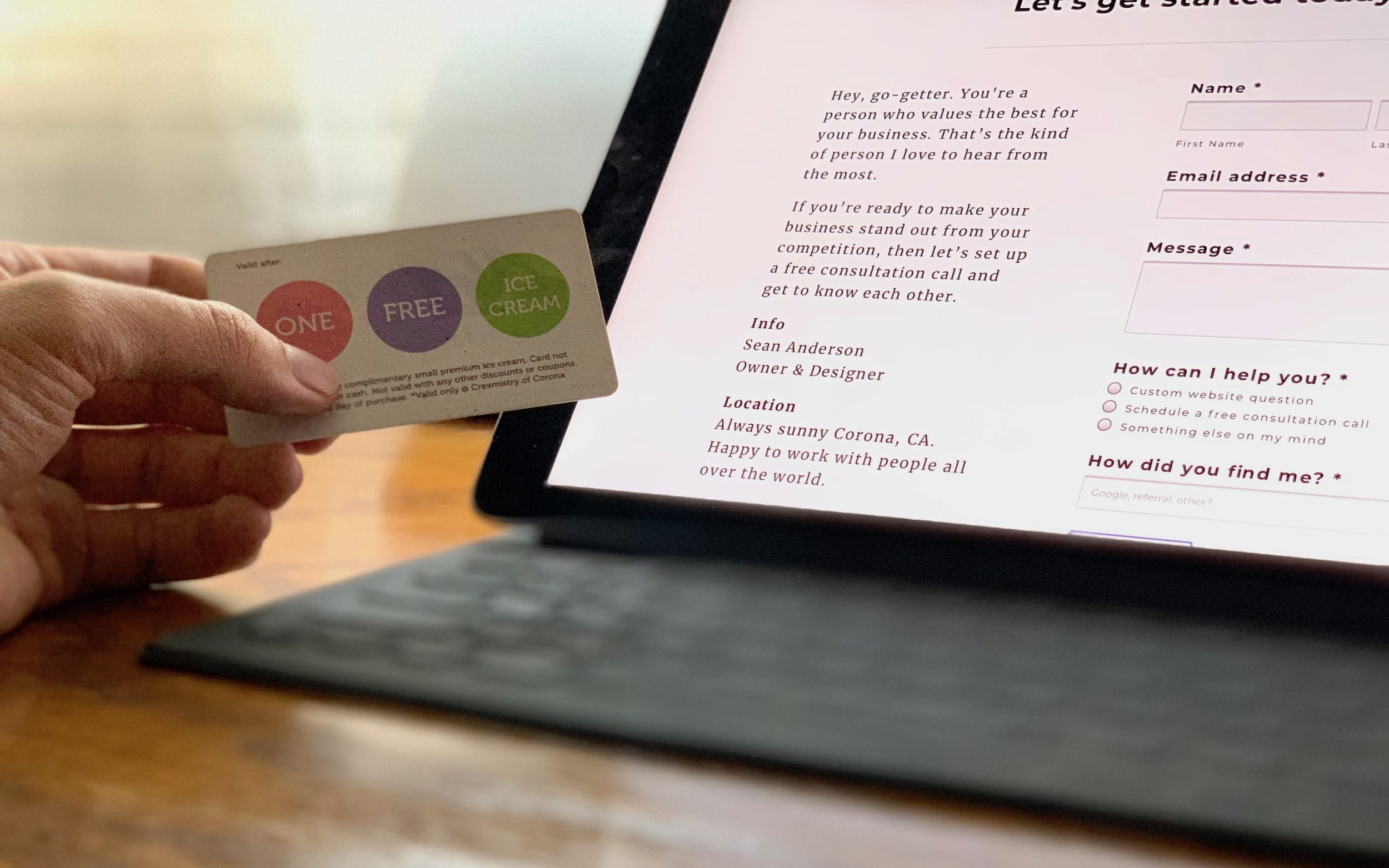 A man's hand holding a loyalty card while looking at a product page.
