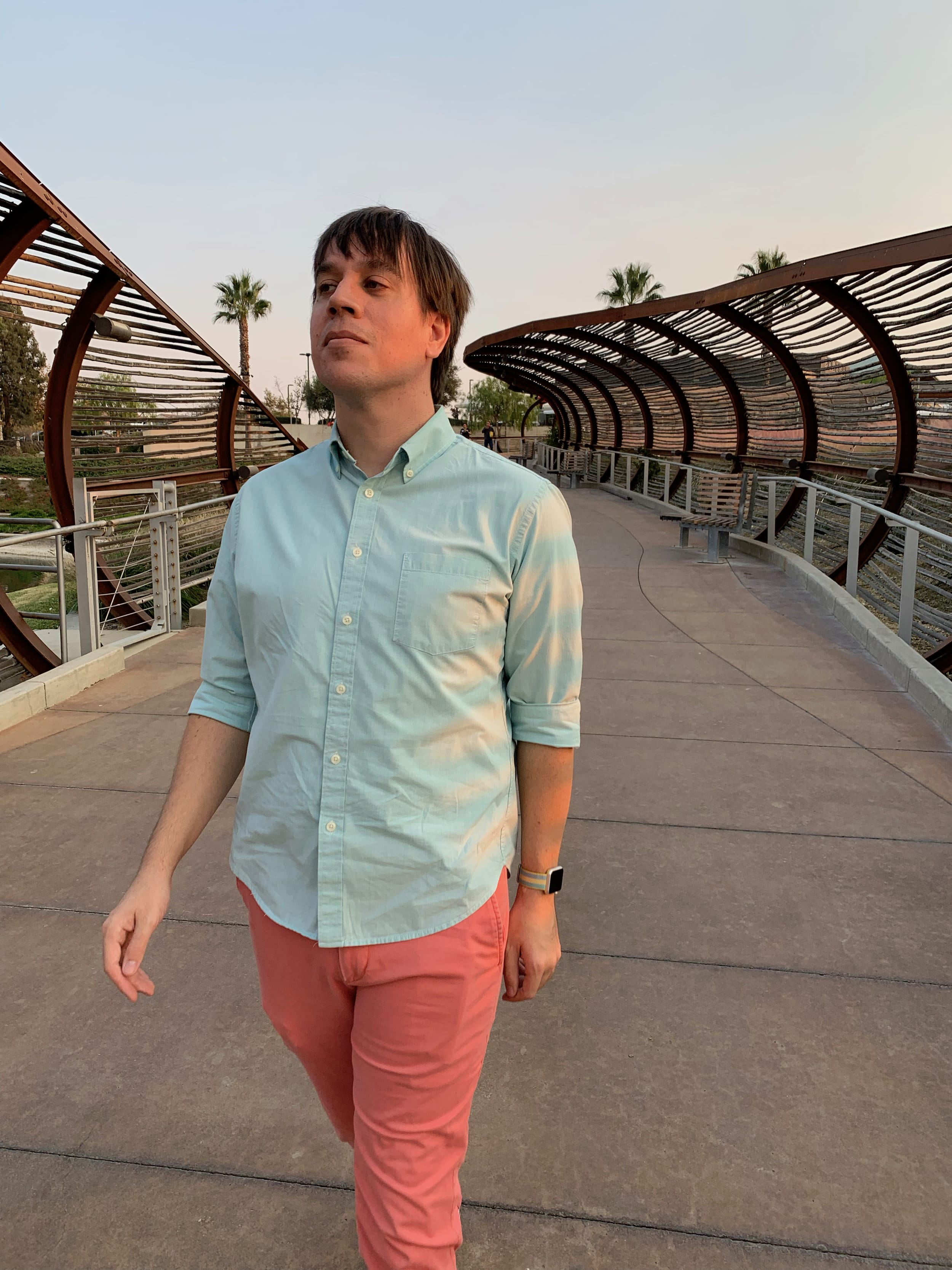 A man wearing a lime green shirt and coral pants walking down a cement walkway under a bamboo overhang.