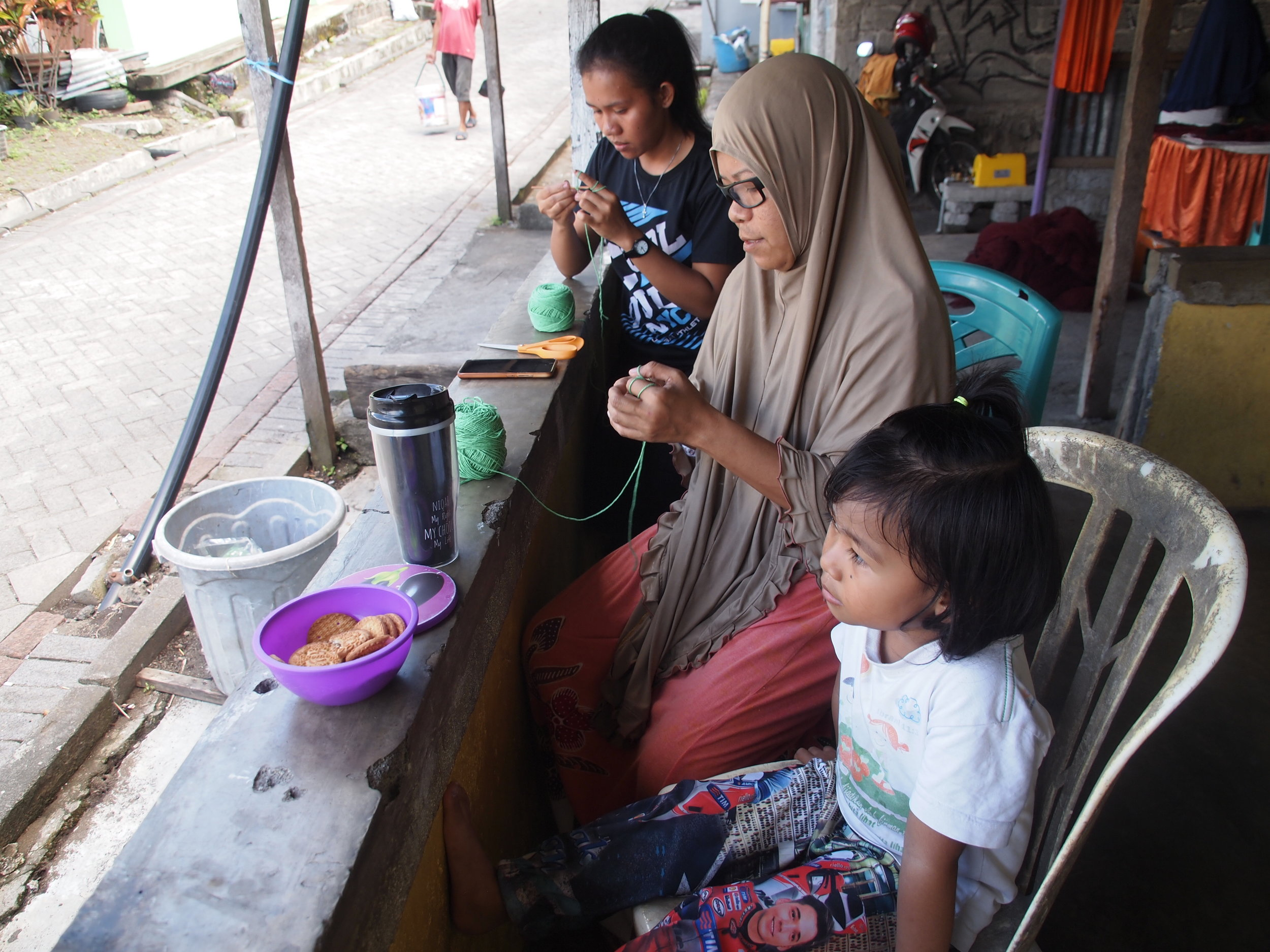 Right to left: Yuli, a student, tried to pull and twist some yarn in crocheting, Ibu Aisya was also doing the same while her daughter enjoyed a bowl of biscuits.