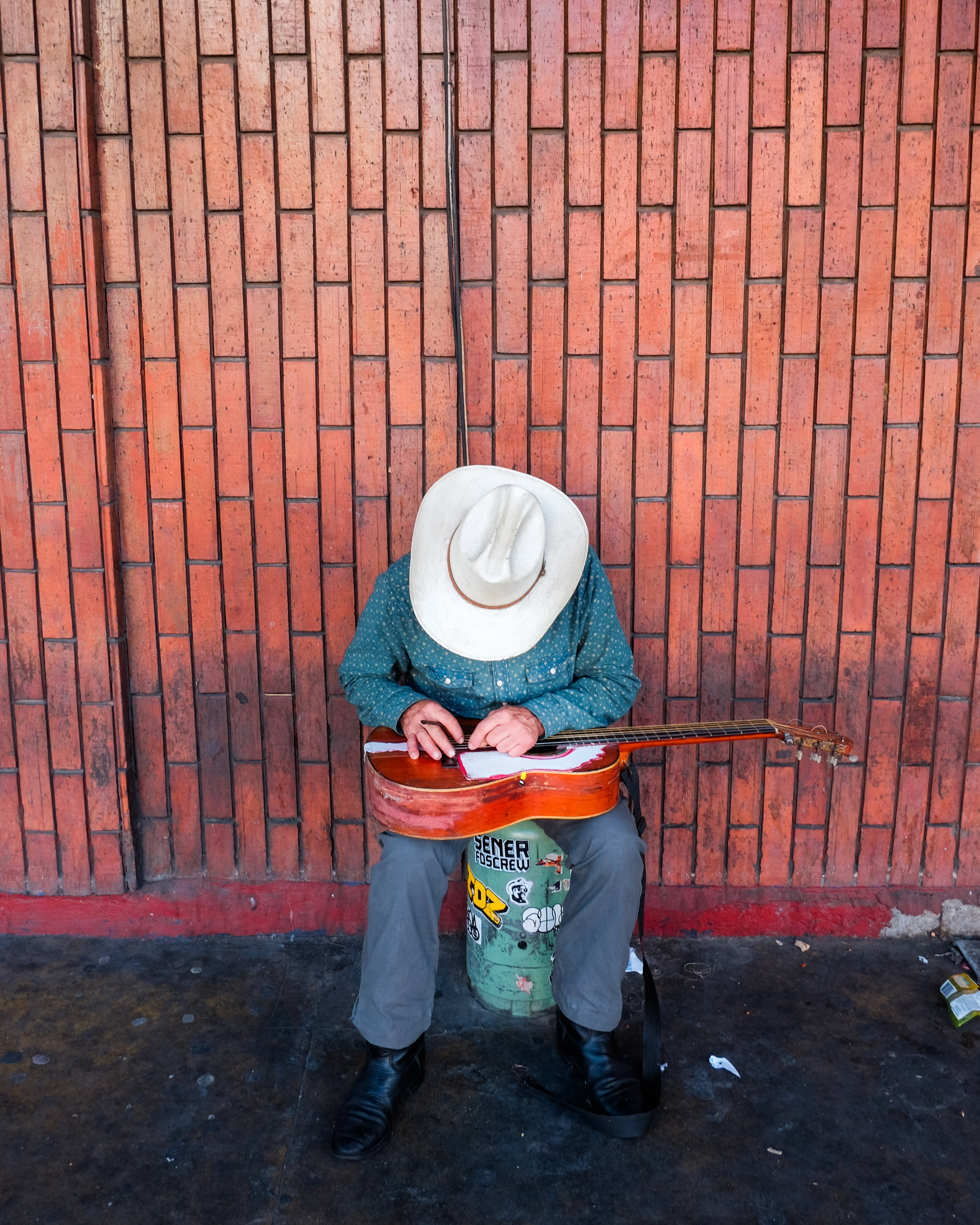 This image was easy as the person was focused on fixing his guitar strings whilst wearing a wide brimmed hat. I had plenty of time to compose the shot and get it right. I took two images altogether. This one and another from a few steps further back. I was there for about 6 seconds total and he was not aware of me in the slightest.
