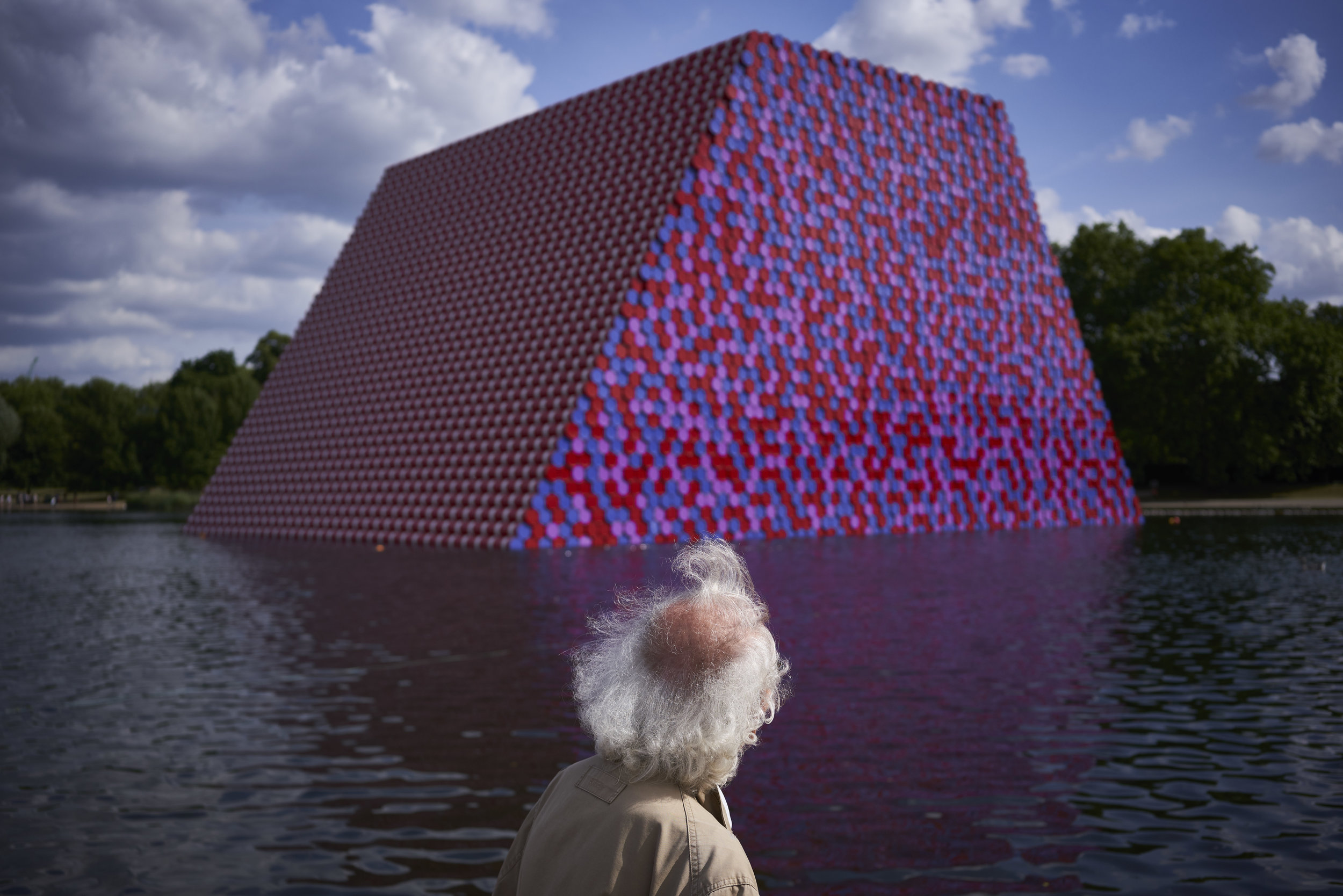 "Christo looks at his completed temporary floating sculpture entitled ""The Mastaba"", which consists of stacked oil barrels, on the Serpentine Lake, Hyde Park, London, England, Friday, June 15, 2018. (David Azia for The New York Times)"