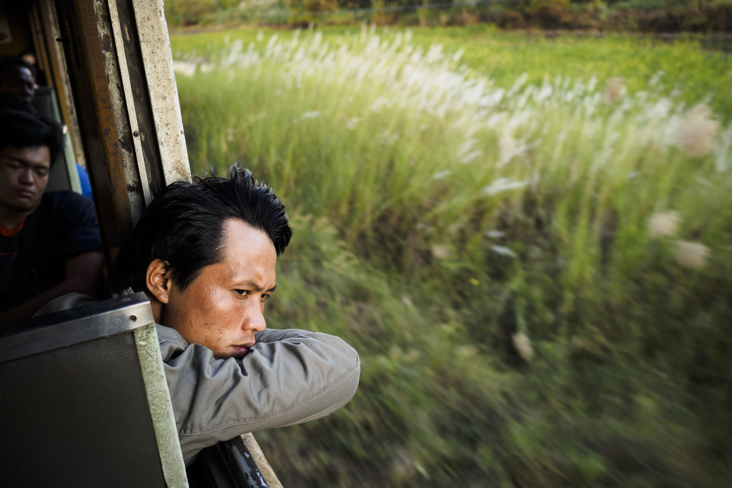 A man looks out of the window of a train running between Aranyaprathet and Bangkok, Thailand, Monday, Nov. 25, 2013.