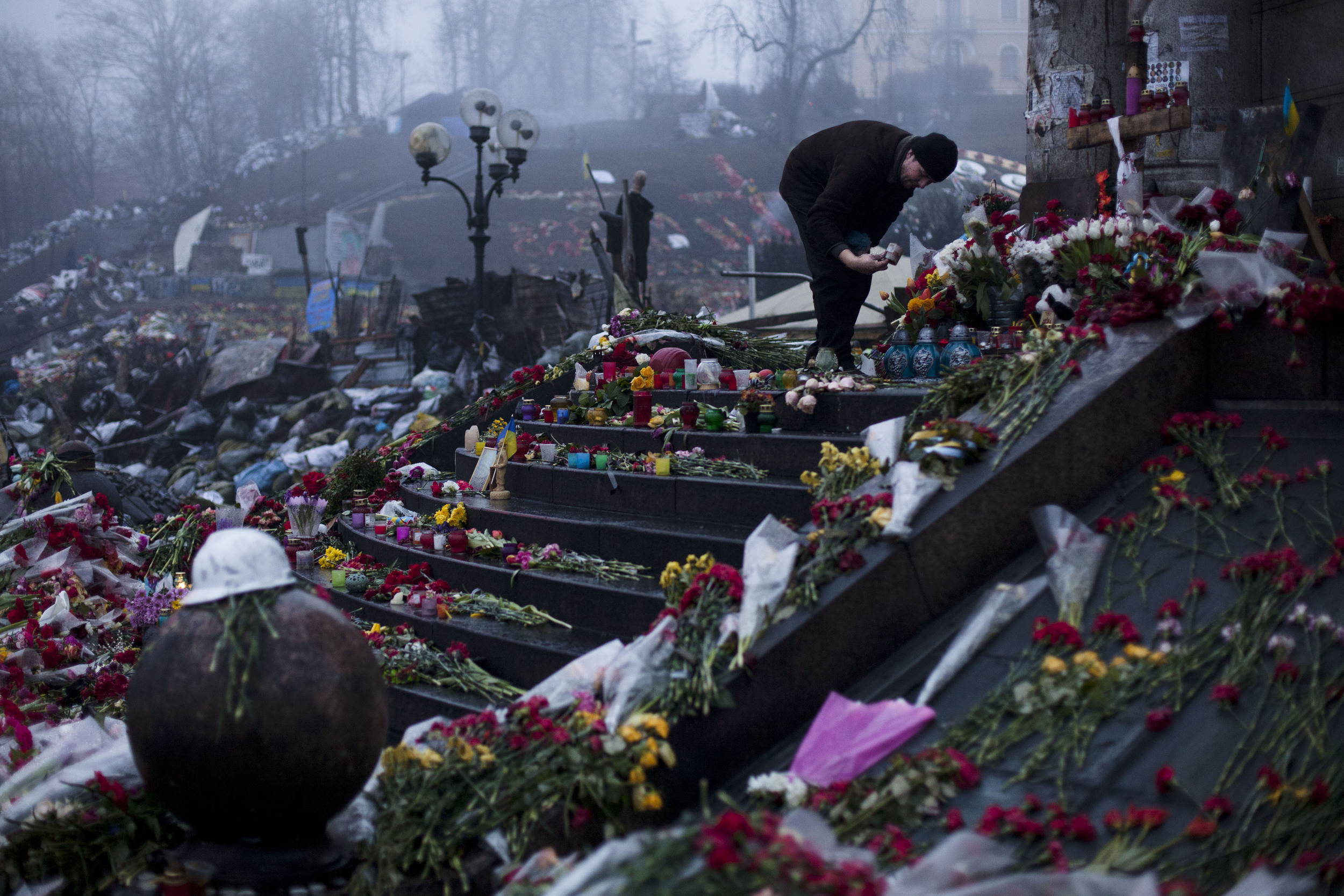 A man arranges candles at a memorial to victims of late February's clashes in Kiev's Independence Square, Ukraine, Wednesday, March 5, 2014. (AP Photo/David Azia)