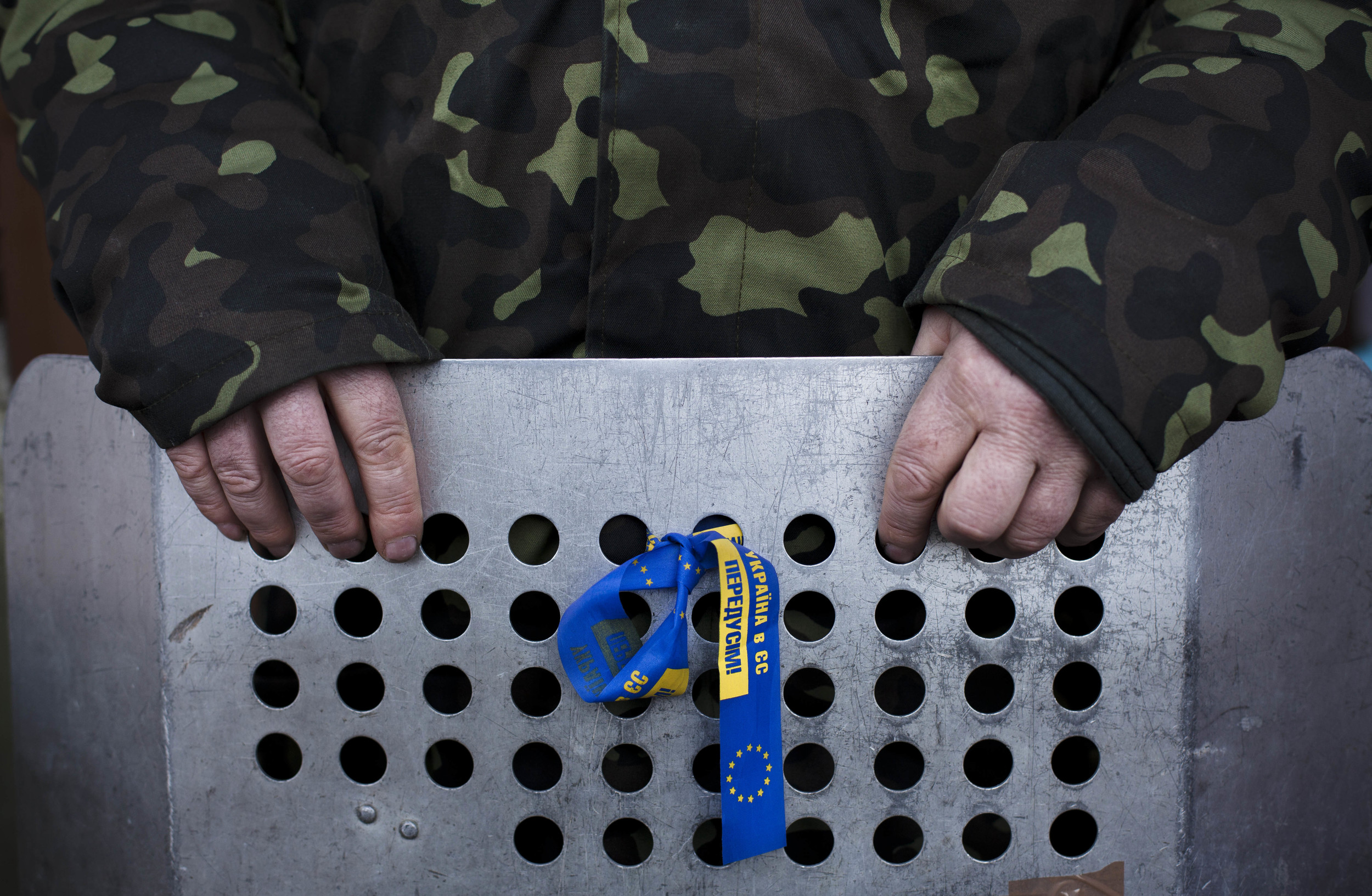 A member of the Right Sector, a Ukrainian far-right opposition group, holds a shield as he stands guard outside a building which is occupied by the movement near Kiev's Independence Square, Ukraine, Sunday, March 9, 2014. (AP Photo/David Azia)