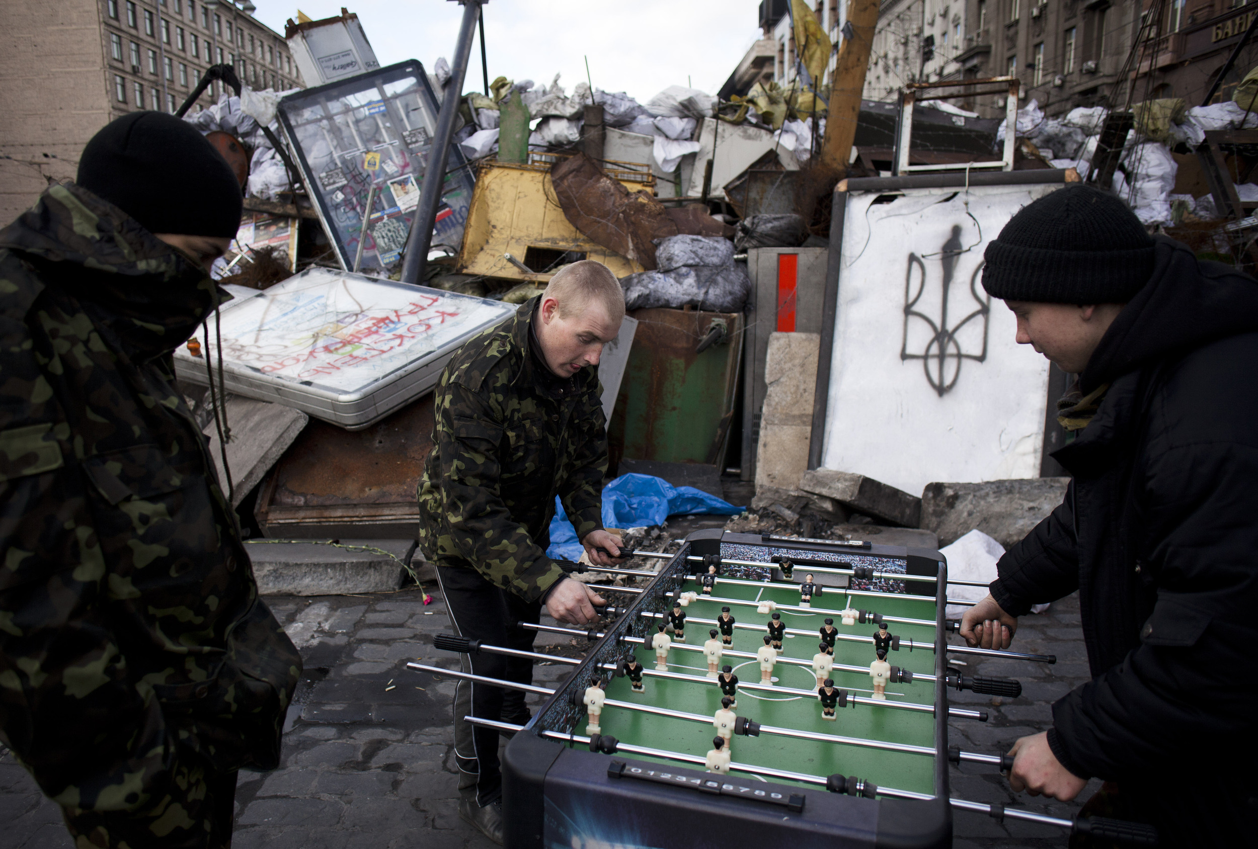 Youths, who are members of a self defense volunteer group, play table football next to a barricade on a road leading to Kiev's Independence Square, Ukraine, Sunday, March 16, 2014. Residents of Ukraine's Crimea region are voting on Sunday in a contentious referendum on whether to split off and seek annexation by Russia. (AP Photo/David Azia)