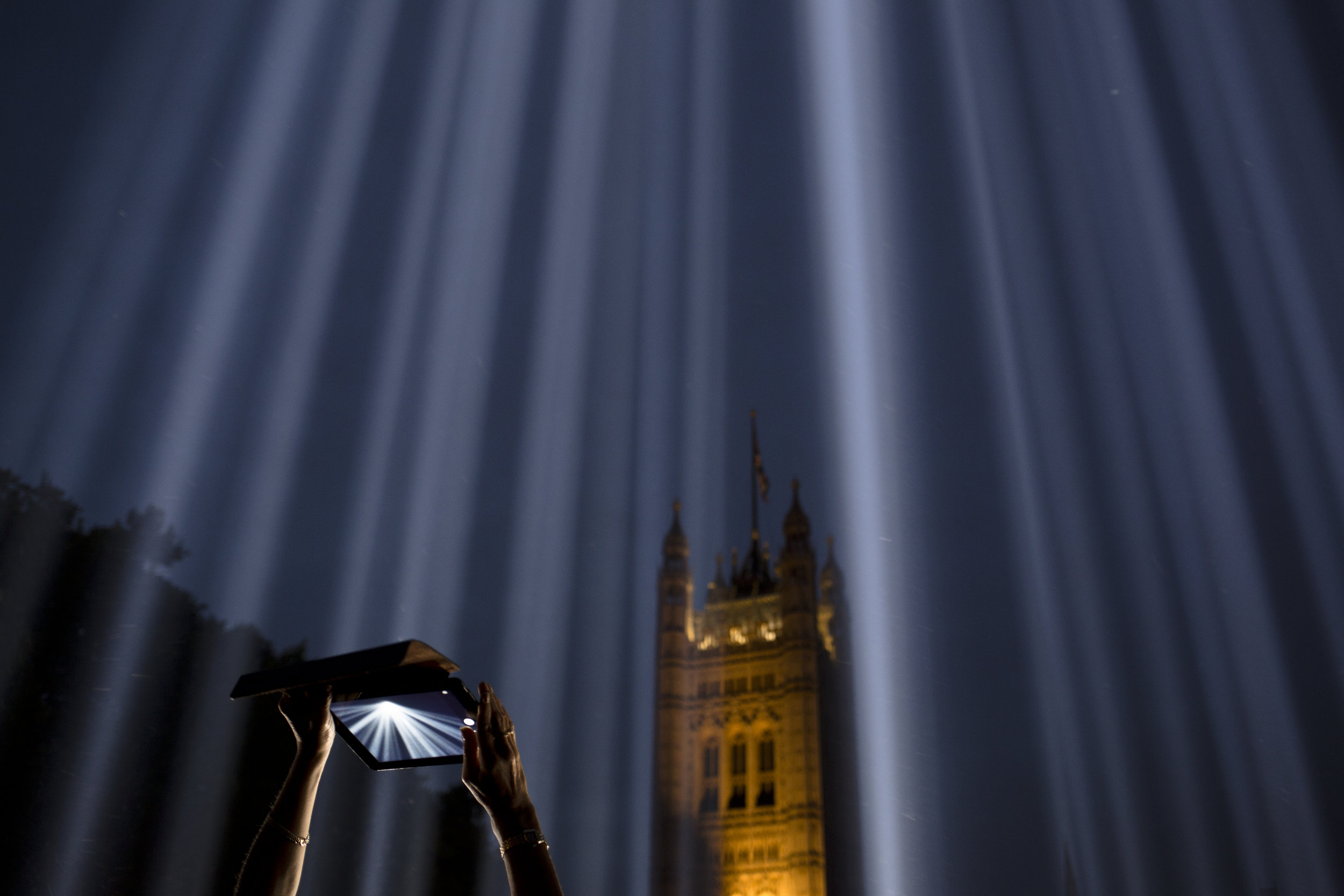 """A woman uses a tablet to photograph shafts of light piercing the night sky at an installation entitled """"Spectra"""" by Japanese artist Ryoji Ikeda outside the Houses of Parliament, London, Tuesday, Aug. 5, 2014. (AP Photo/David Azia)"""