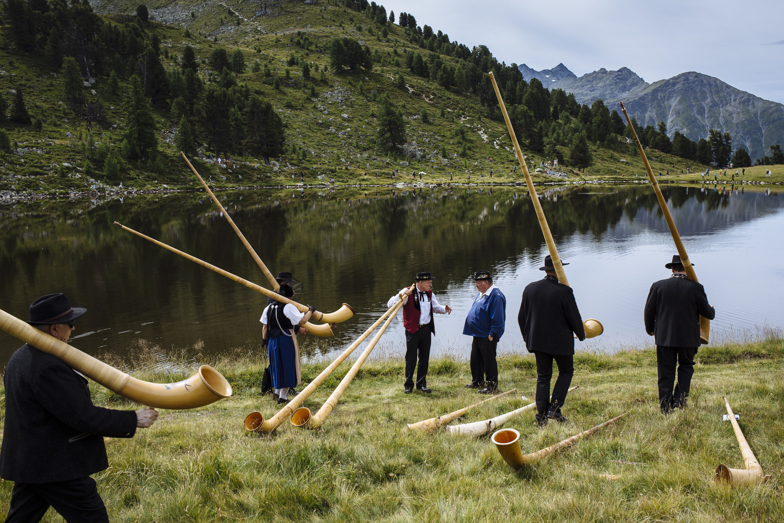 Alpenhorn players carry their instruments following a performance with 245 hornists as they walk along the Lac de Tracouet, situated 2200 meters (7220 feet) above sea level in Haute-Nendaz, canton of Valais, Switzerland, Sunday, July 26, 2015. (AP Photo/David Azia)