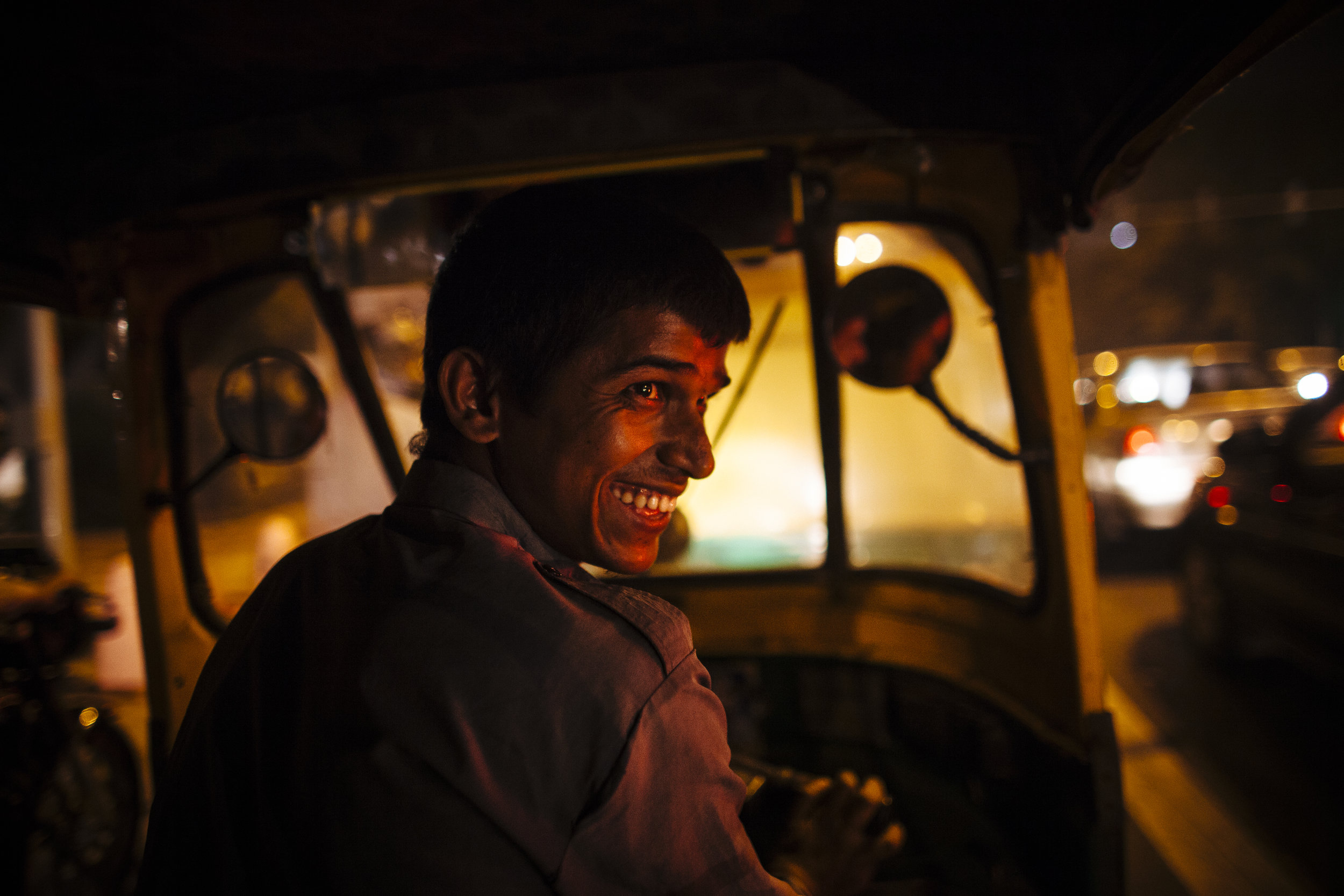An auto-rickshaw drive smiles as he negotiates evening traffic during the Commonwealth Games in New Delhi, India, Wednesday, Oct. 6, 2010.