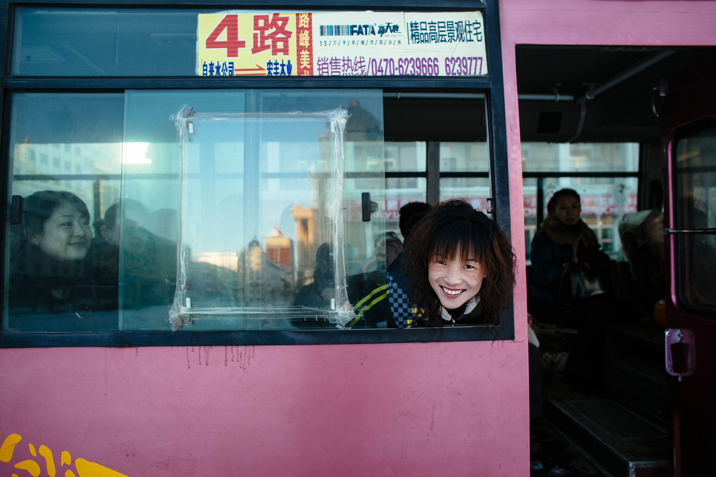 A woman calling for passengers on a bus smiles as she poses for a photograph in Manzhouli, Inner Mongolia, China, Saturday, March 21, 2009.