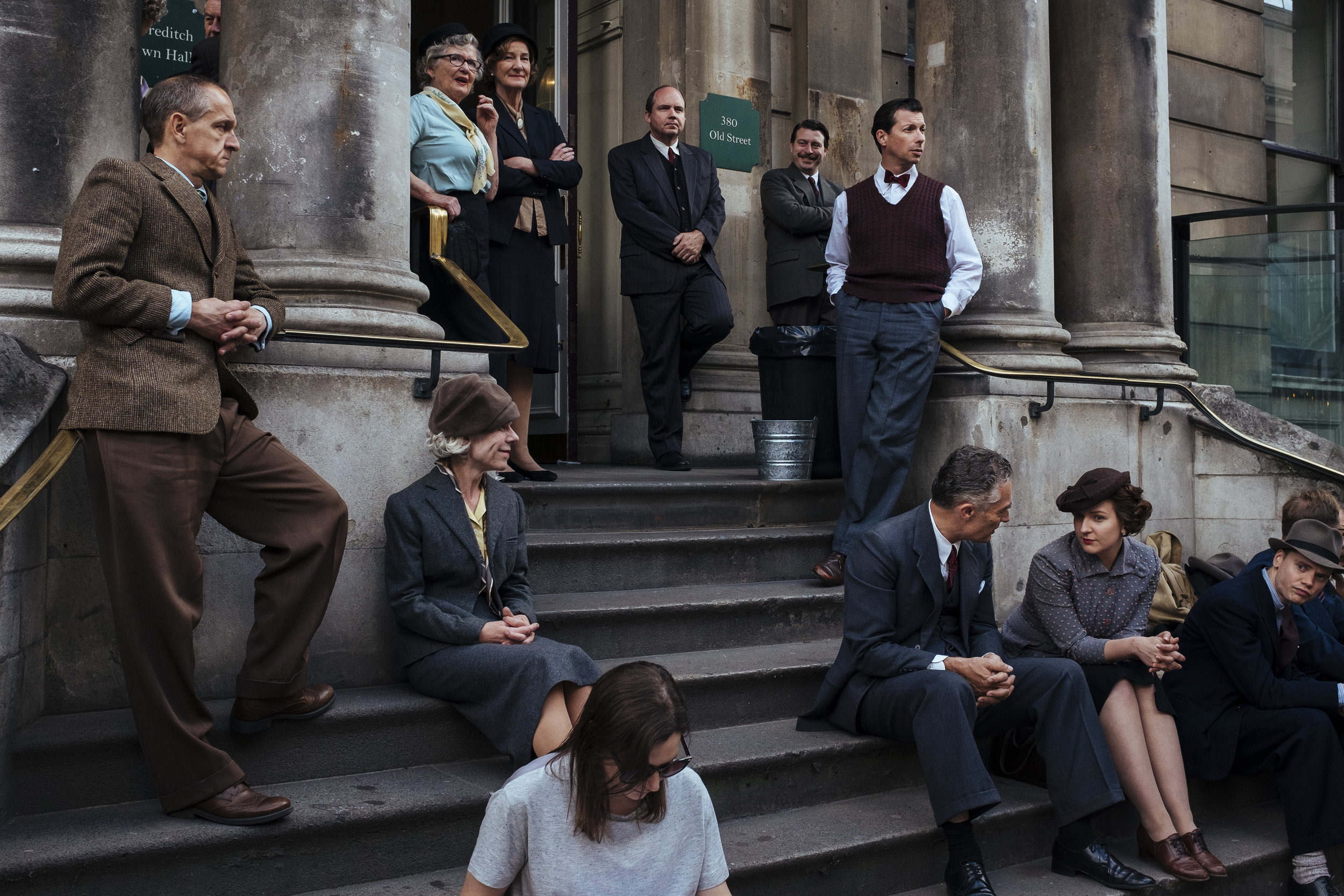 """The cast of a television film production entitled """"Churchill's Secret"""" wear period costumes as they take a break from filming outside Shoreditch Town Hall, London, Sunday, June 21, 2015."""