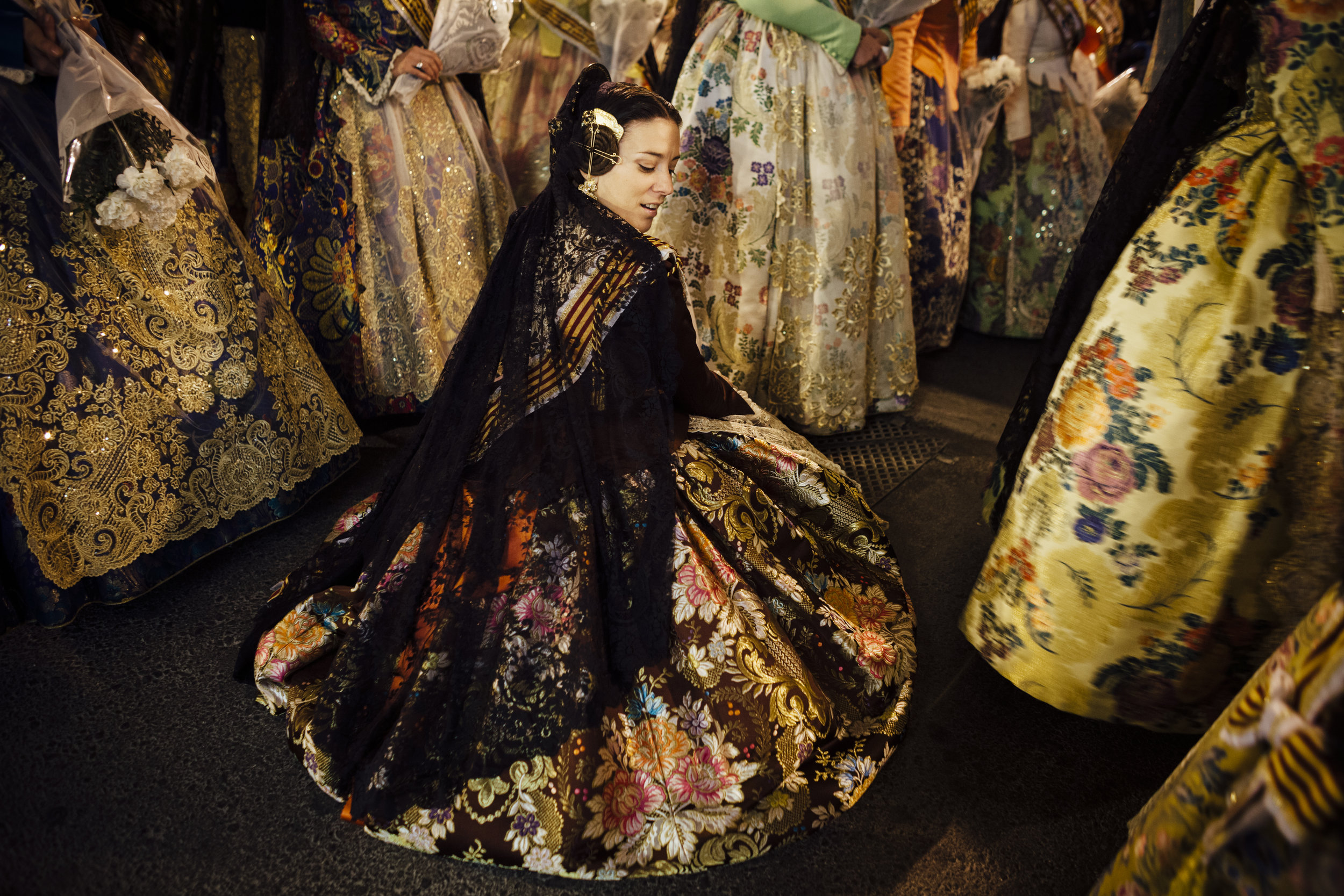 A woman participating in the Fallas, a traditional celebration held in commemoration of Saint Joseph, sits on the ground in Valencia, Spain, Thursday, March 18, 2010.