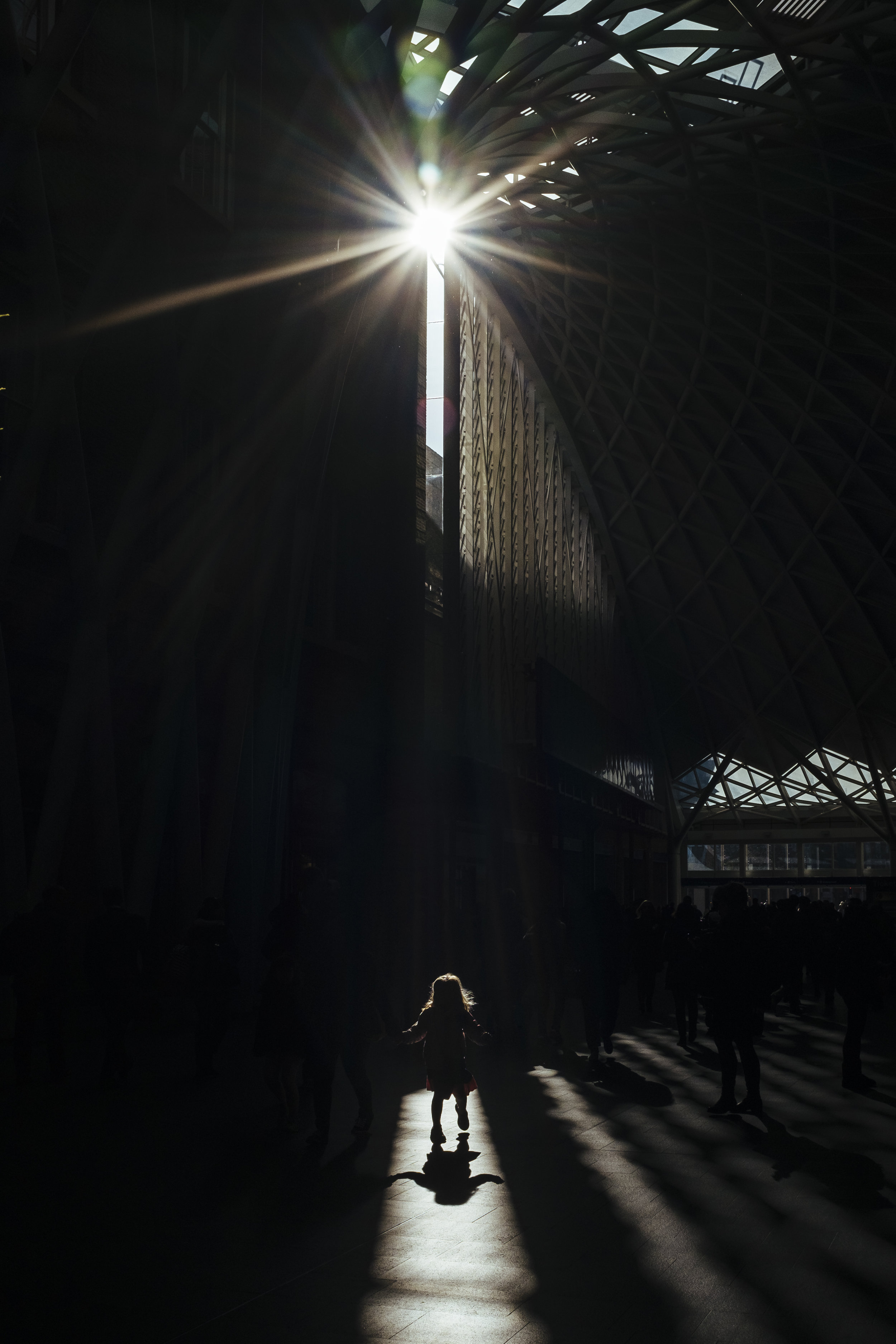 A girl walks in a shaft of light on the main concourse at King's Cross railway station, London, Wednesday, Feb. 18, 2015.