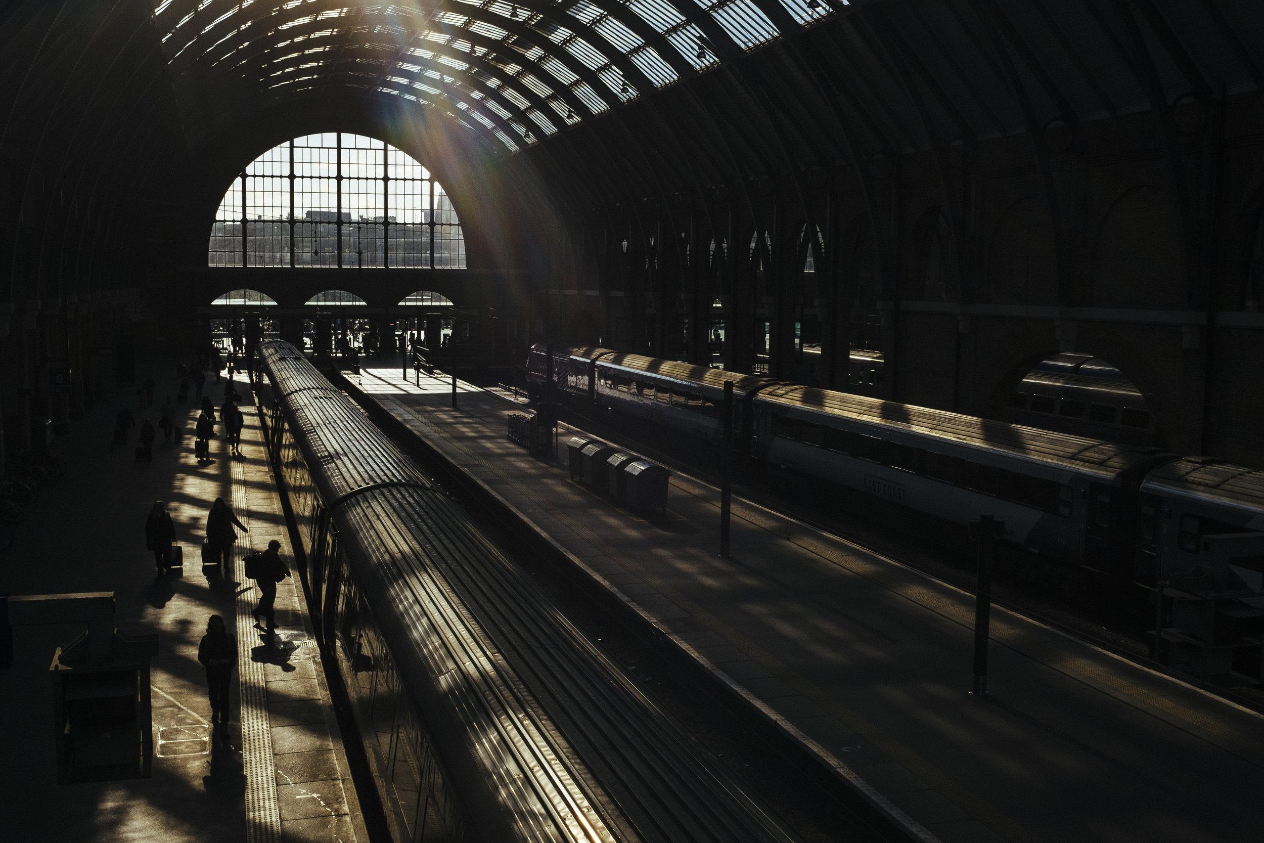 Passengers walk alongside a waiting train at a platform at King's Cross railway station, London, Wednesday, Feb. 18, 2015.