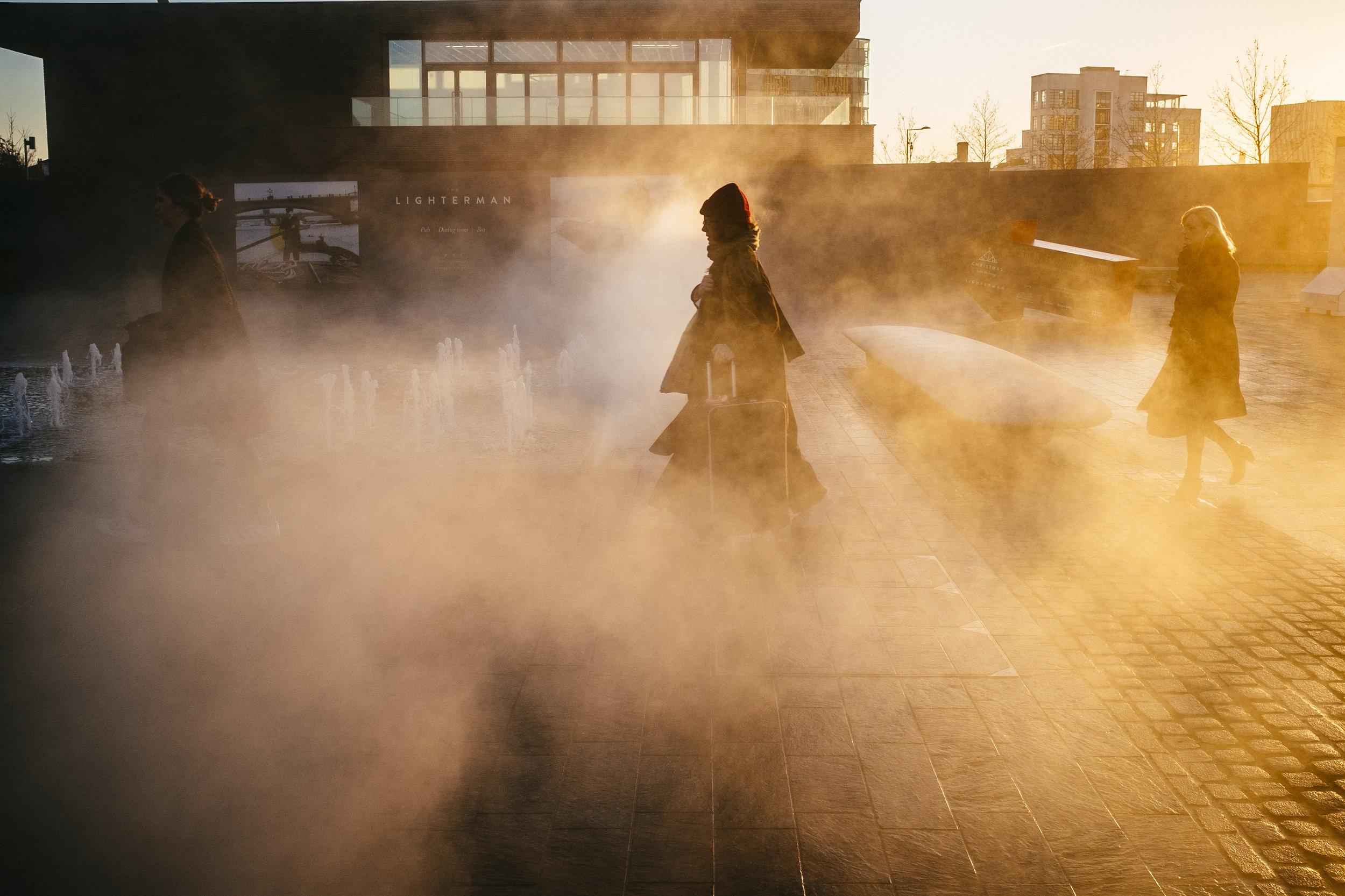 Pedestrians walks through steam rising from a fountain on Granary Square, near King's Cross, London, Wednesday, Dec. 9, 2015.