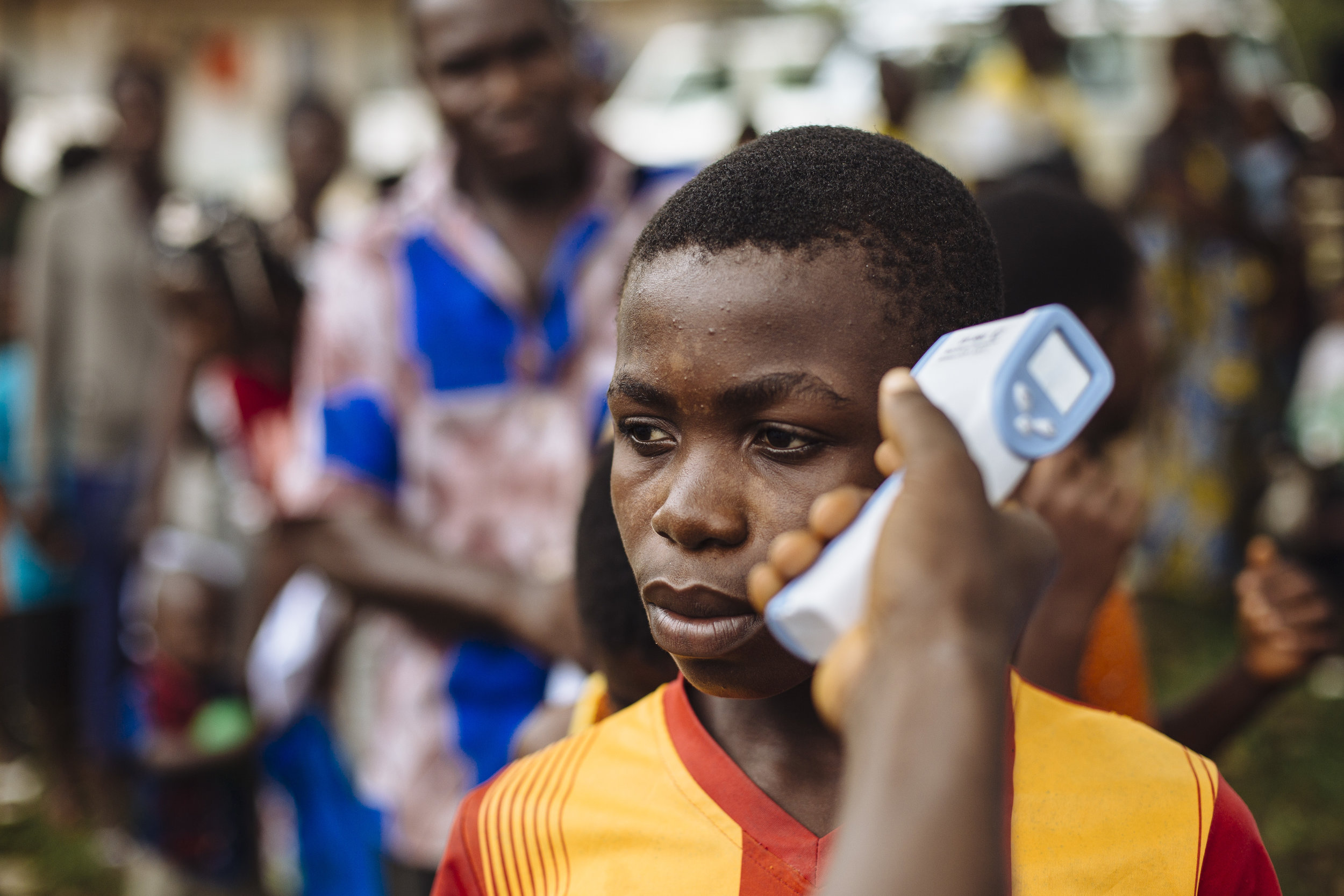 Deeke Toussaint Hie has his temperature recorded, part of efforts to prevent the transmission of the Ebola Virus Disease, at a border post near the Cavalla River, which demarcates the border with Côte d'Ivoire, in Maryland, Liberia.