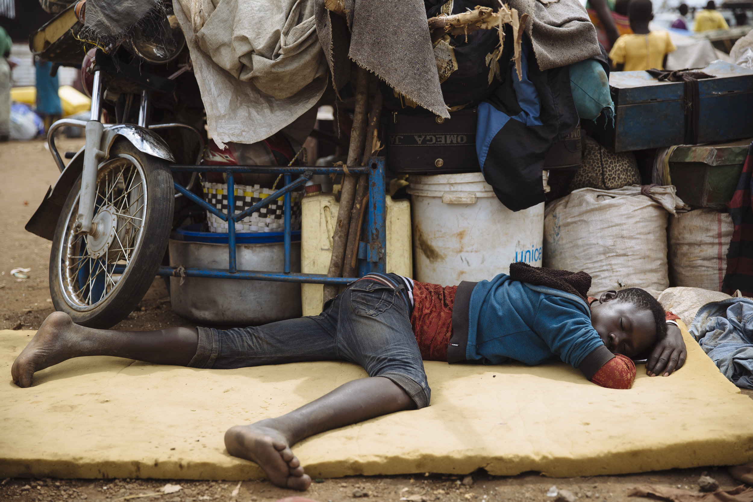 A South Sudanese refugee sleeps on a mattress alongside personal belongings at the Imvepi Reception Centre, Arua District, Northern Region, Uganda.