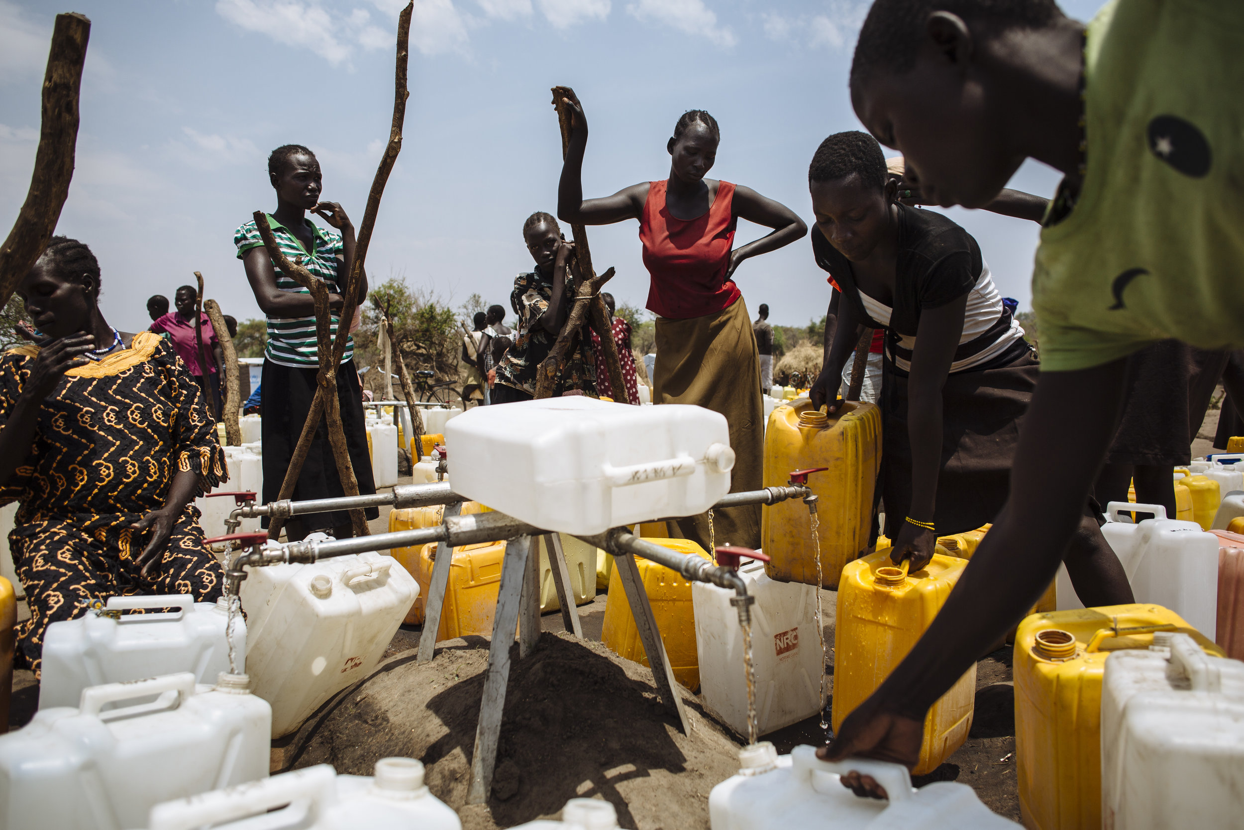 South Sudanese refugees fill jerry cans with water from a water point in Bidibidi refugee settlement, Yumbe District, Northern Region, Uganda. Fetching water often involves hours of waiting due to high demand, despite the tank being filled twice daily by a water truck.