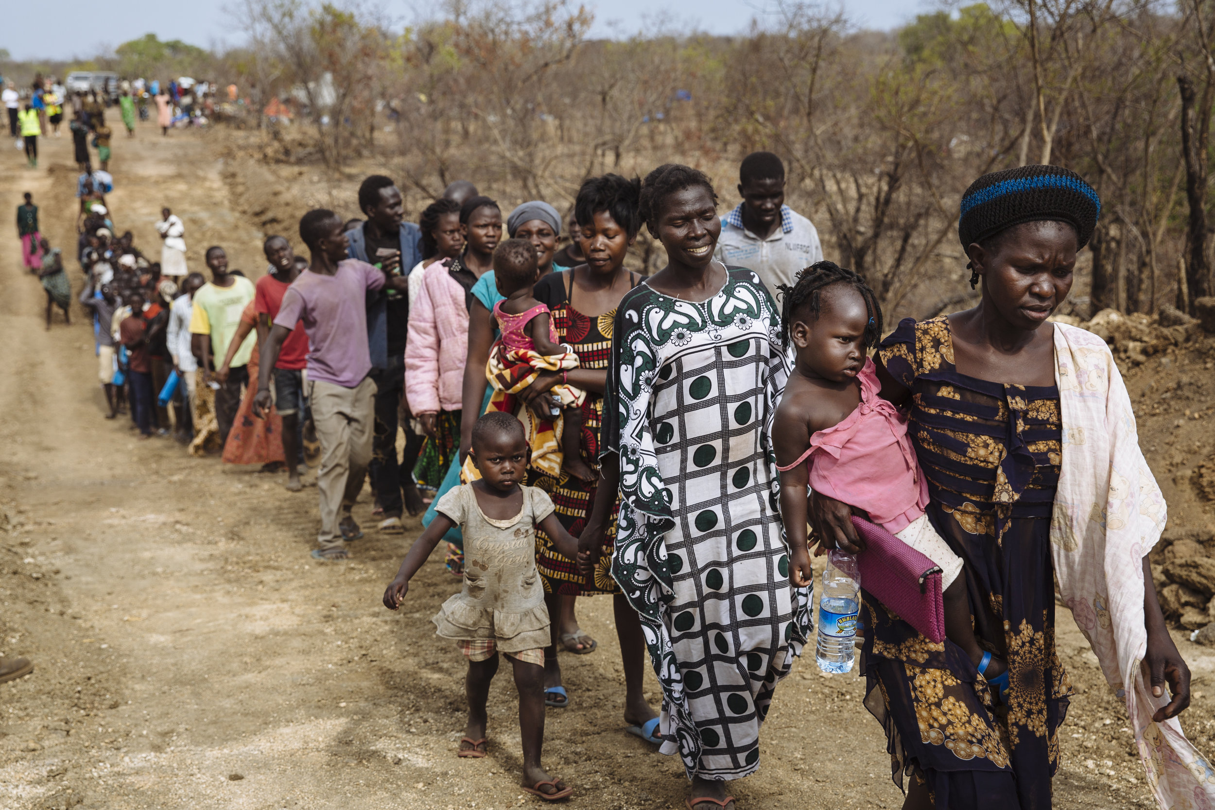 South Sudanese refugee Opani Lilias, 28, right, carries her only child Brenda, 21 months, as they follow a plot allocator along a dirt road at the recently established Imvepi settlement, Arua District, Northern Region, Uganda.