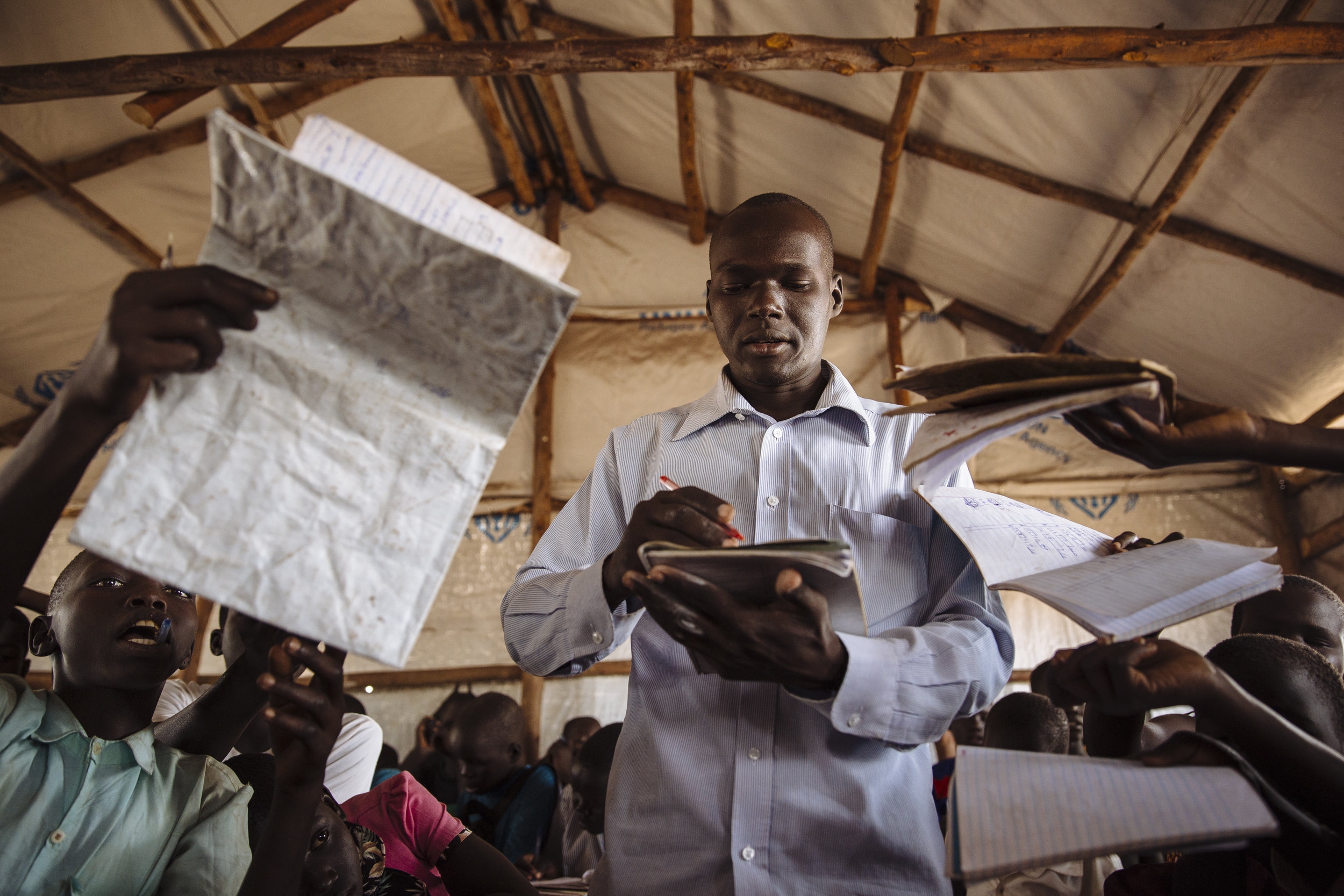 A teacher checks the work of his students during a mathematics class at the Ofonze Primary School in Bidibidi refugee settlement, Yumbe District, Northern Region, Uganda.