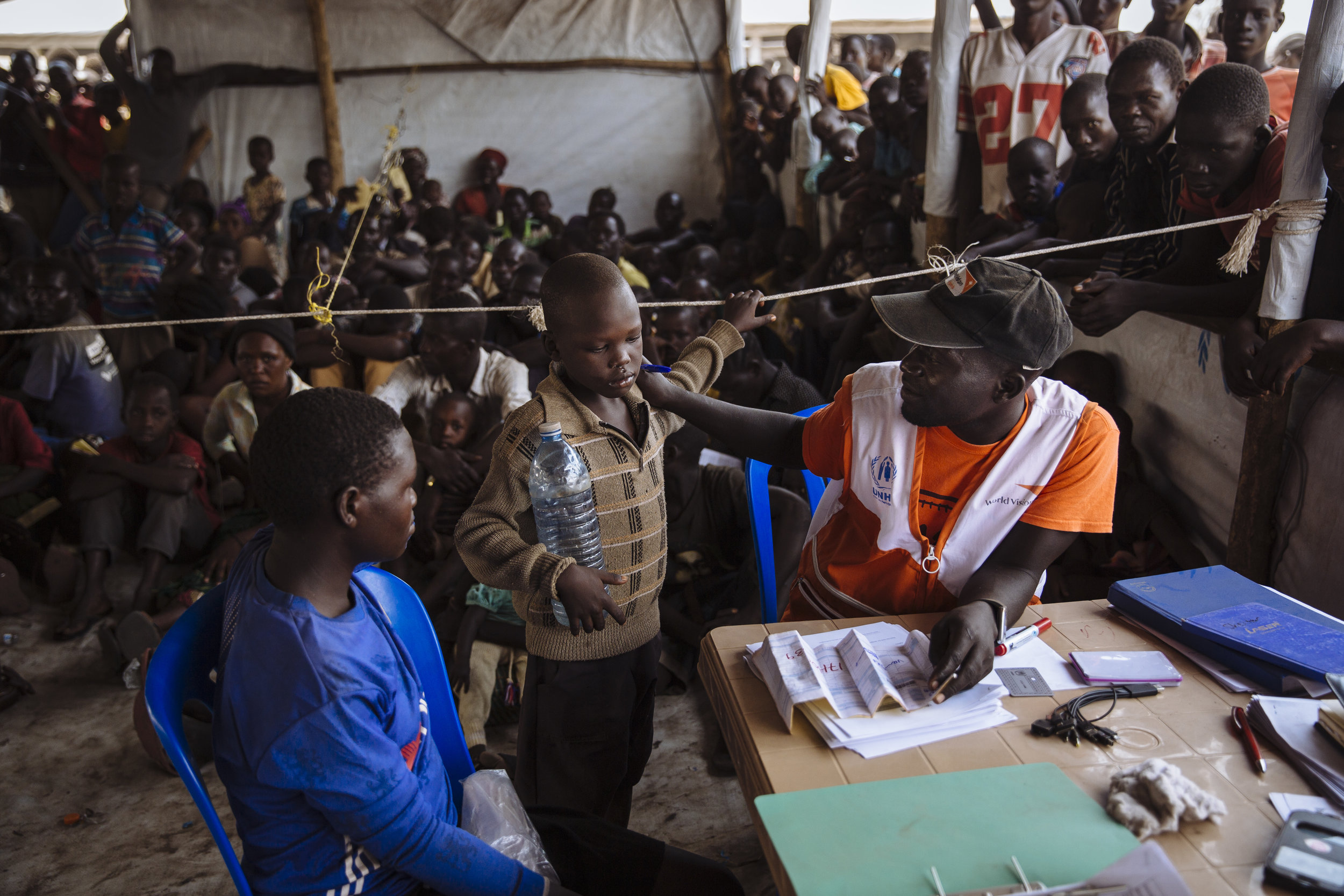 A UNHCR partner, right, speaks with a South Sudanese refugee as he registers a family at the Imvepi Reception Centre, Arua District, Northern Region, Uganda.