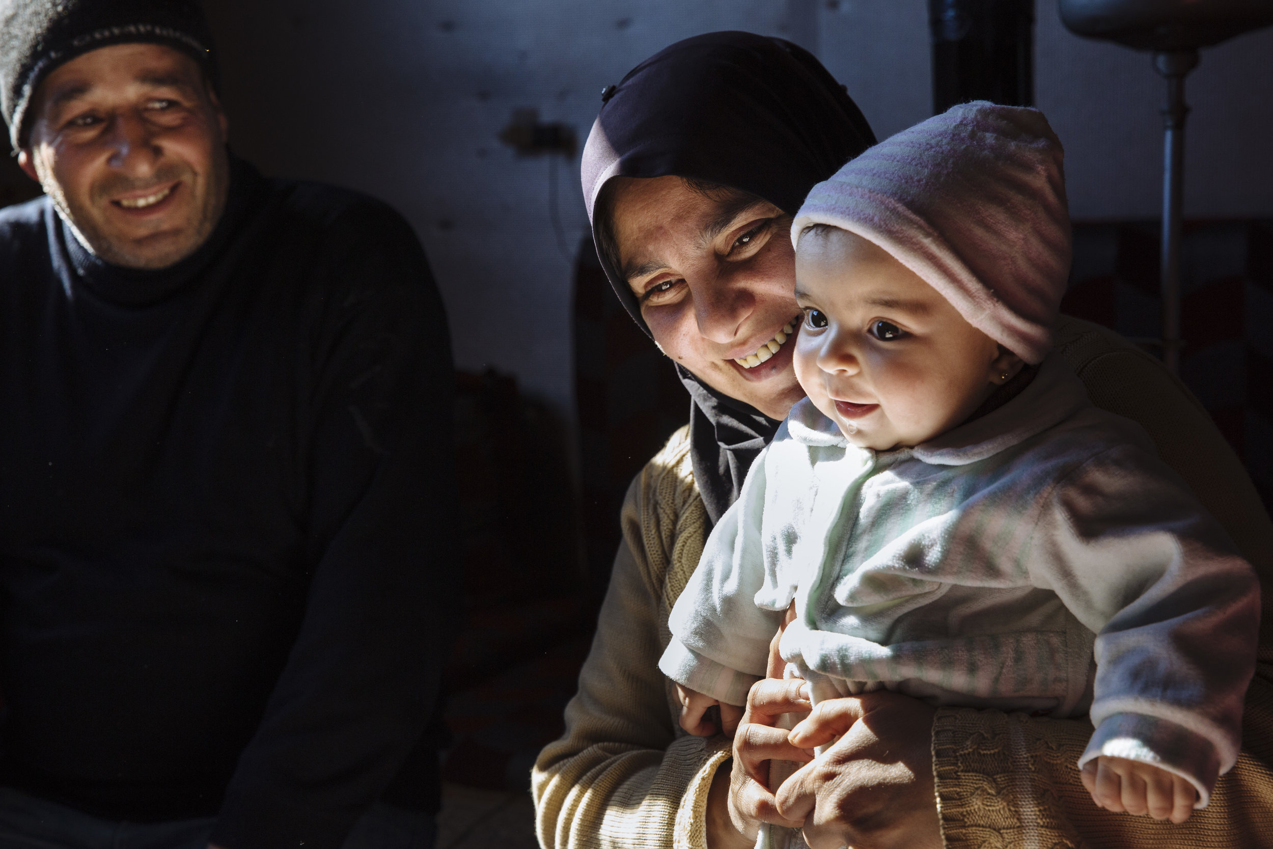 Syrian refugee Samira, 38, holds her six-month-old niece Mona alongside her husband Khaled, 45, a Palestinian refugee displaced from Syria, on the floor of the substandard apartment they share with their family, in Barelias, Bekaa Valley, Lebanon.
