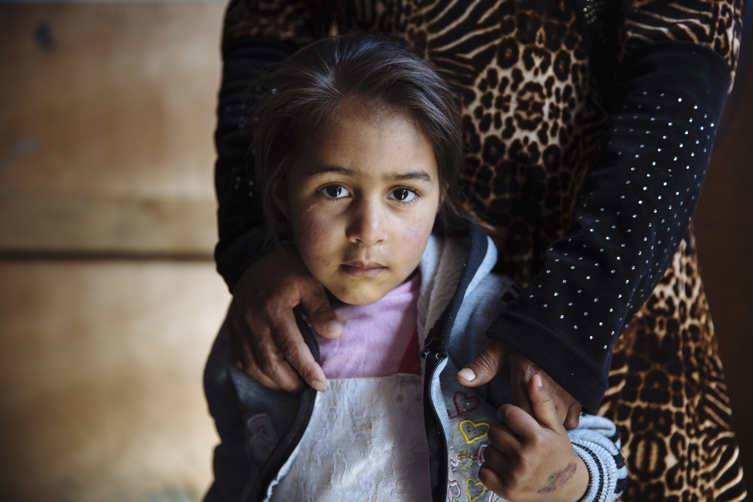 Syrian refugee Raghad, 4, stands with her mother Halima, 37, a mother of nine from rural Aleppo, inside their shelter at an informal settlement near Barelias, Bekaa Valley, Lebanon. Halima received winterization assistance in order to weatherproof her shelter from the harsh winter.